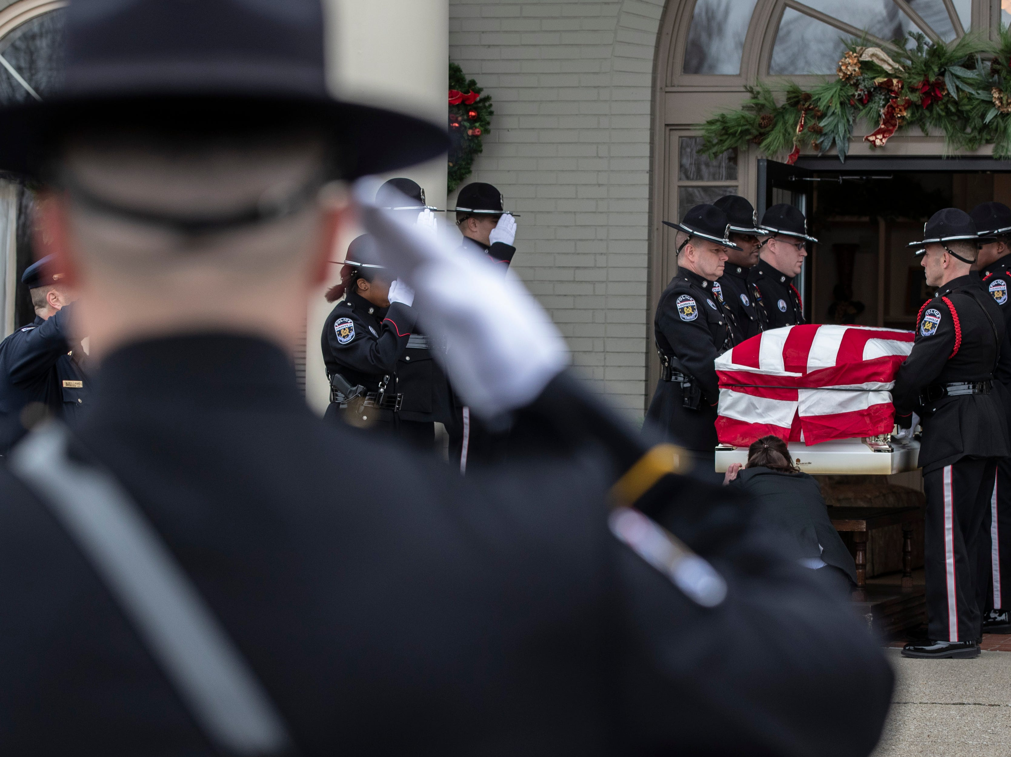 Police officers salute as the coffin of Deidre Mengedoht is carried into the Resthaven Funeral Home on Bardstown Road in Louisville, Ky. December 29, 2018