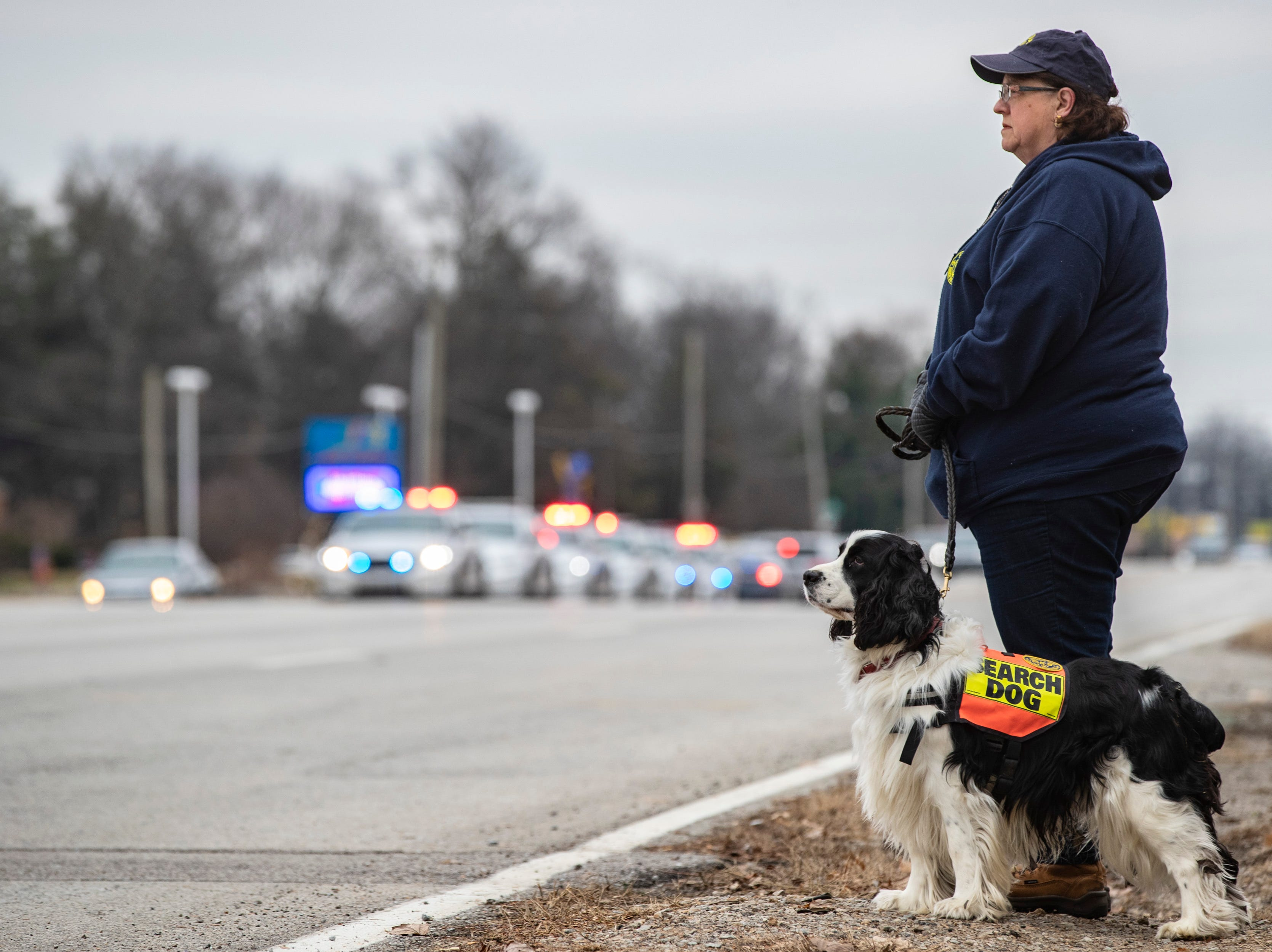 Aleta Eldridge with the Jefferson County Search Dog Association stands with Quincy awaiting the procession of Det. Deidre Mengedoht as it reaches the Resthaven Funeral Home on Bardstown Road in Louisville, Ky. December 29, 2018