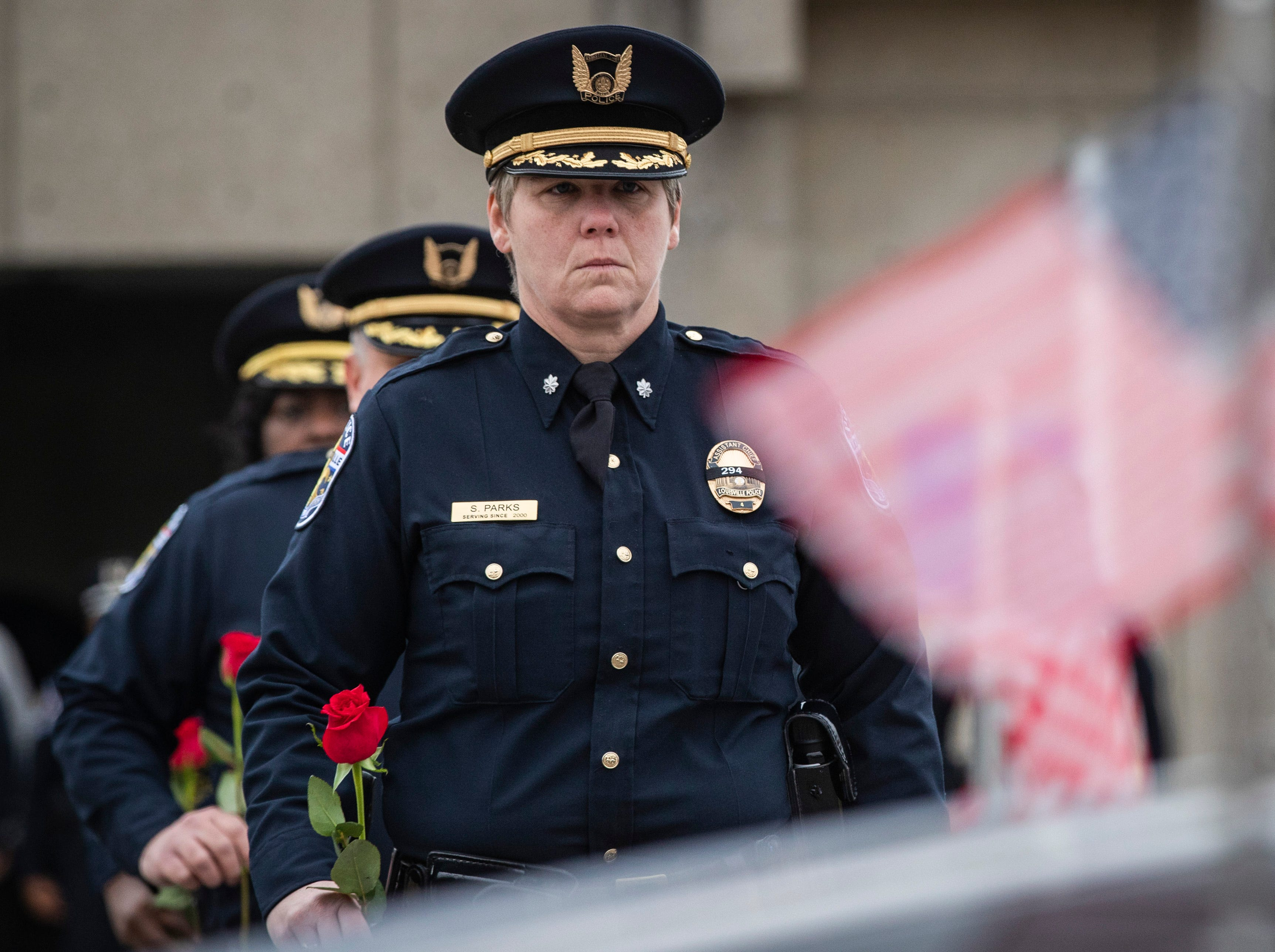 LMPD assistant chief of police, Shara Parks, carries a rose to be placed on the hearse carrying Det. Deidre Mengedoht during a stop at the LMPD 2nd Division headquarters in Park DuValle. December 29, 2018