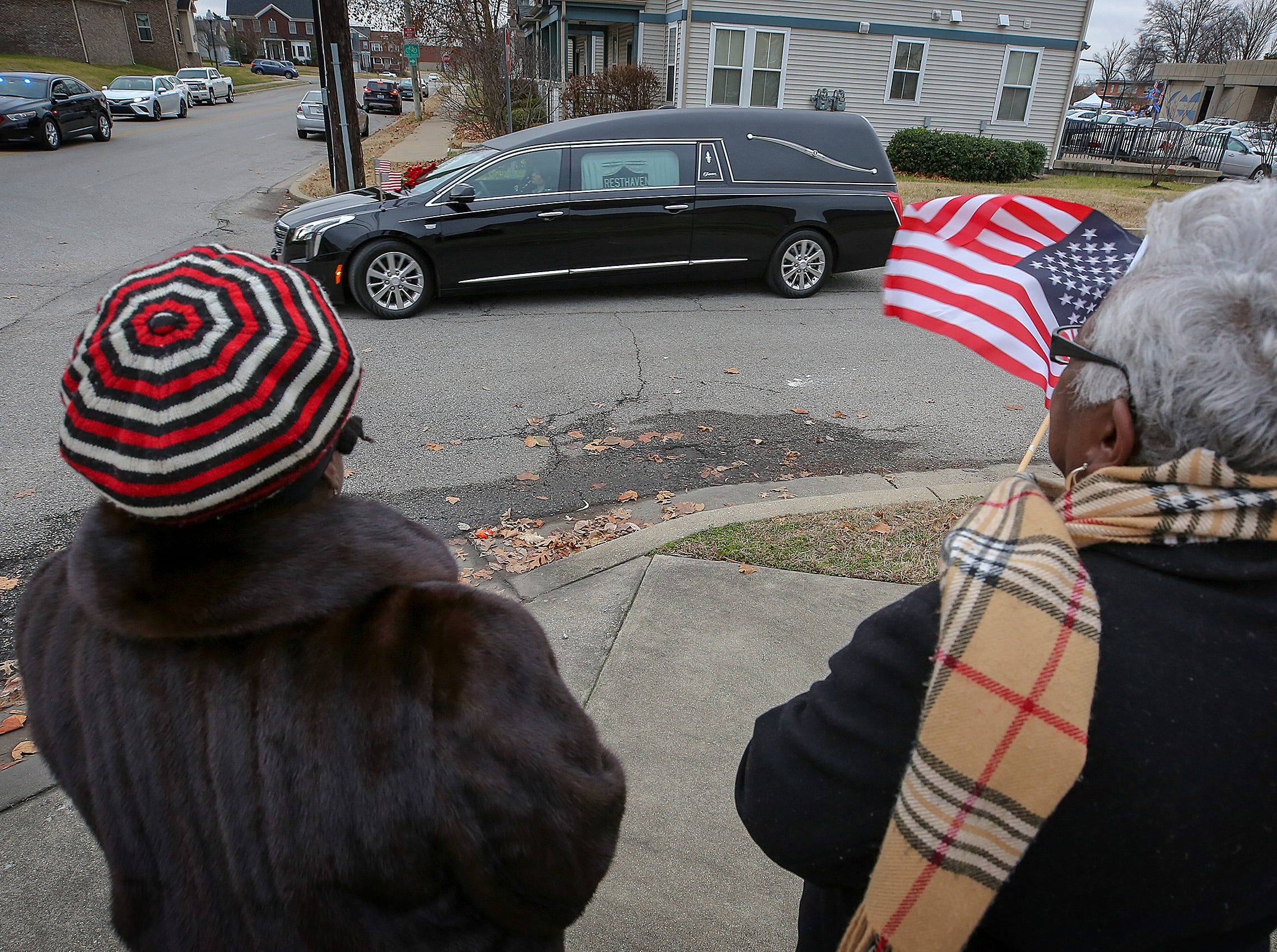 "Catharine Sands, left, and her aunt, Sandra Marshall, right, wave a flag as they said, ""Thank you for your service,"" as the hearse of Deidre Mengedoht drove through Park DuValle after a stop at the police sub station."