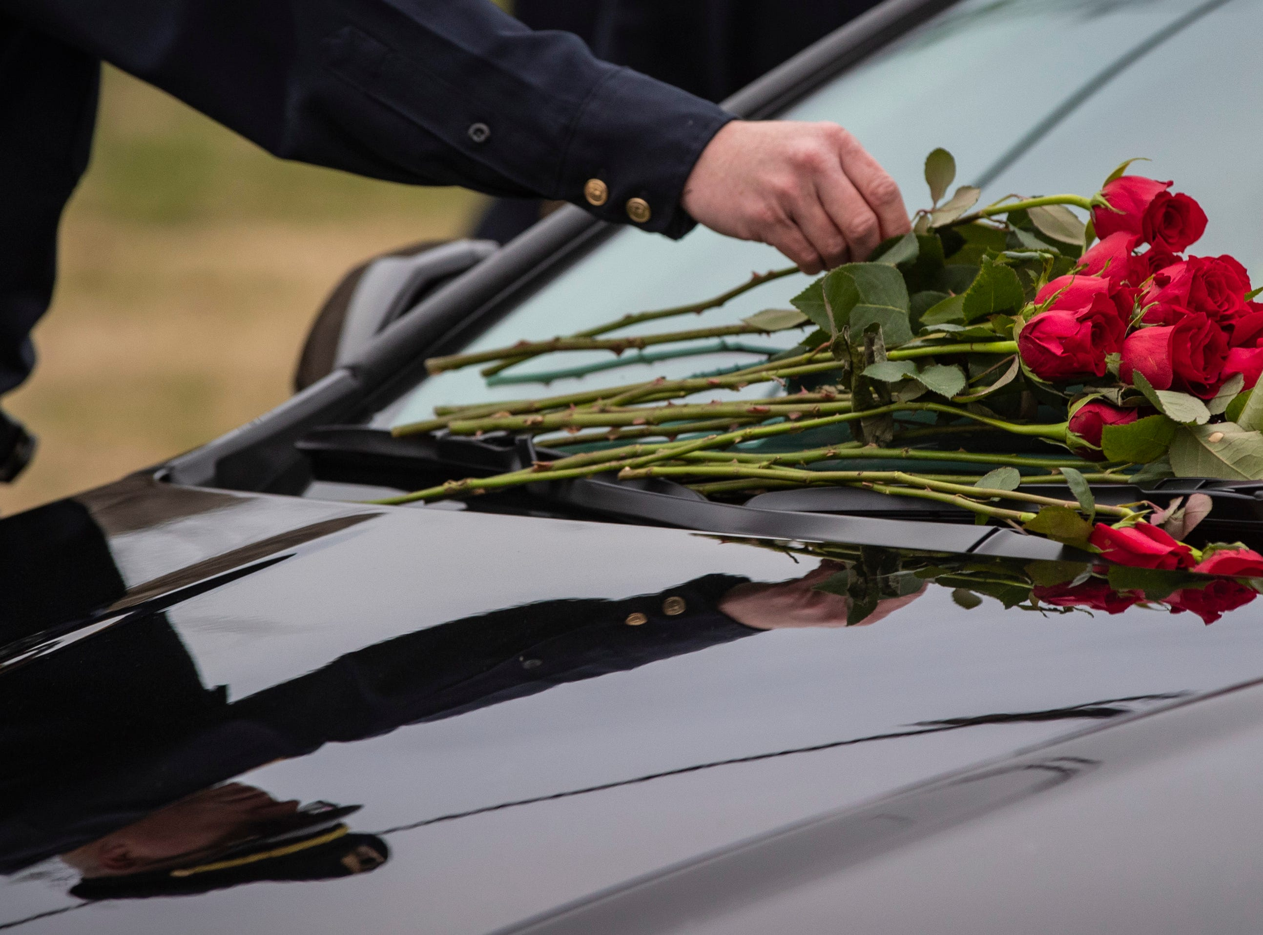 LMPD officers lay roses on the hearse carrying Det. Deidre Mengedoht during a stop at the LMPD 2nd Division headquarters in Park DuValle. December 29, 2018