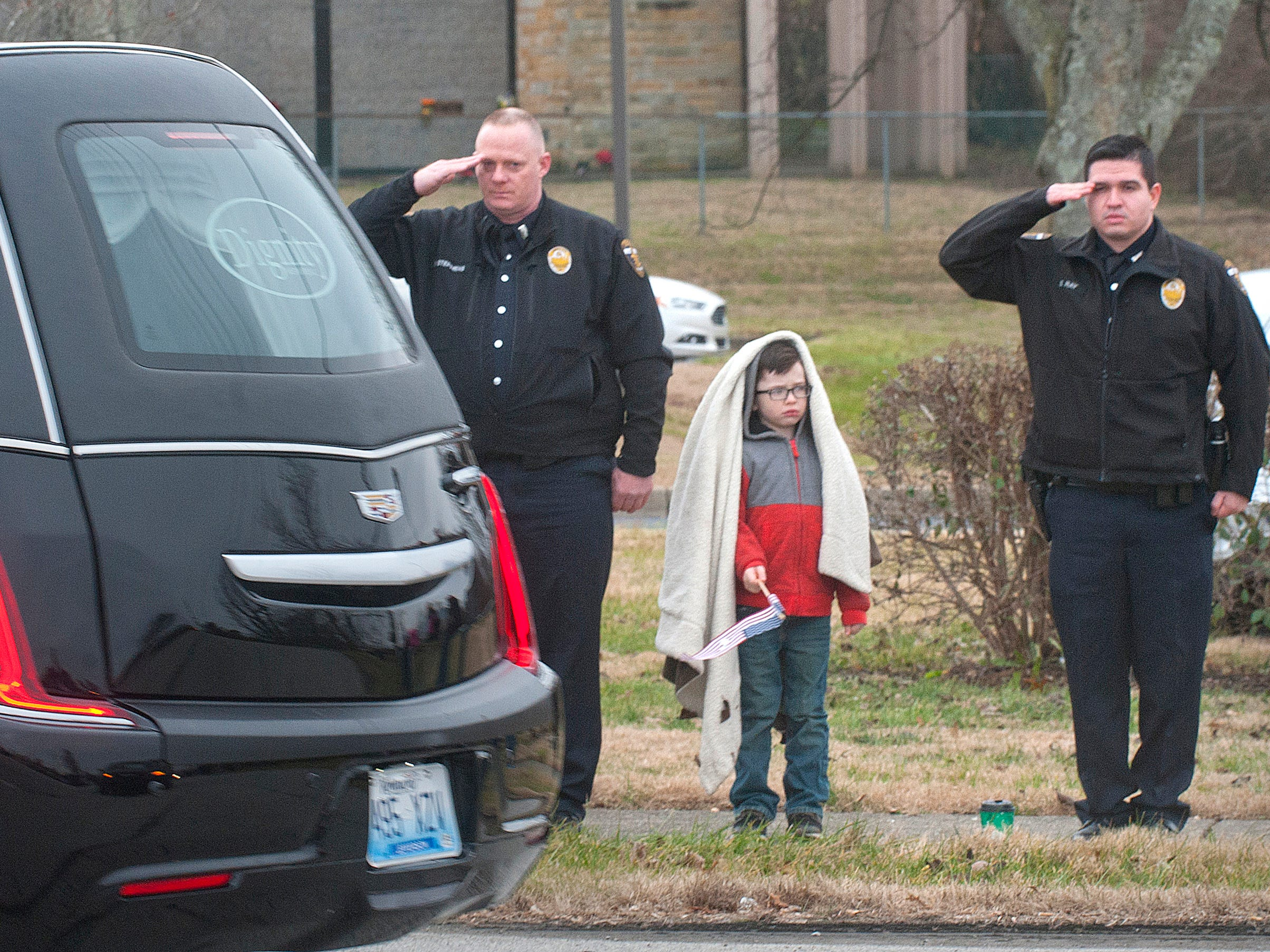 Metro Corrections Officers R. Stephn, left, and S. Ray, right, salute as the casket of LMPD Detective Deidre Mengedoht passes. Ray's son, Andrew, age 6, center, watches the processional. 29 December 2018