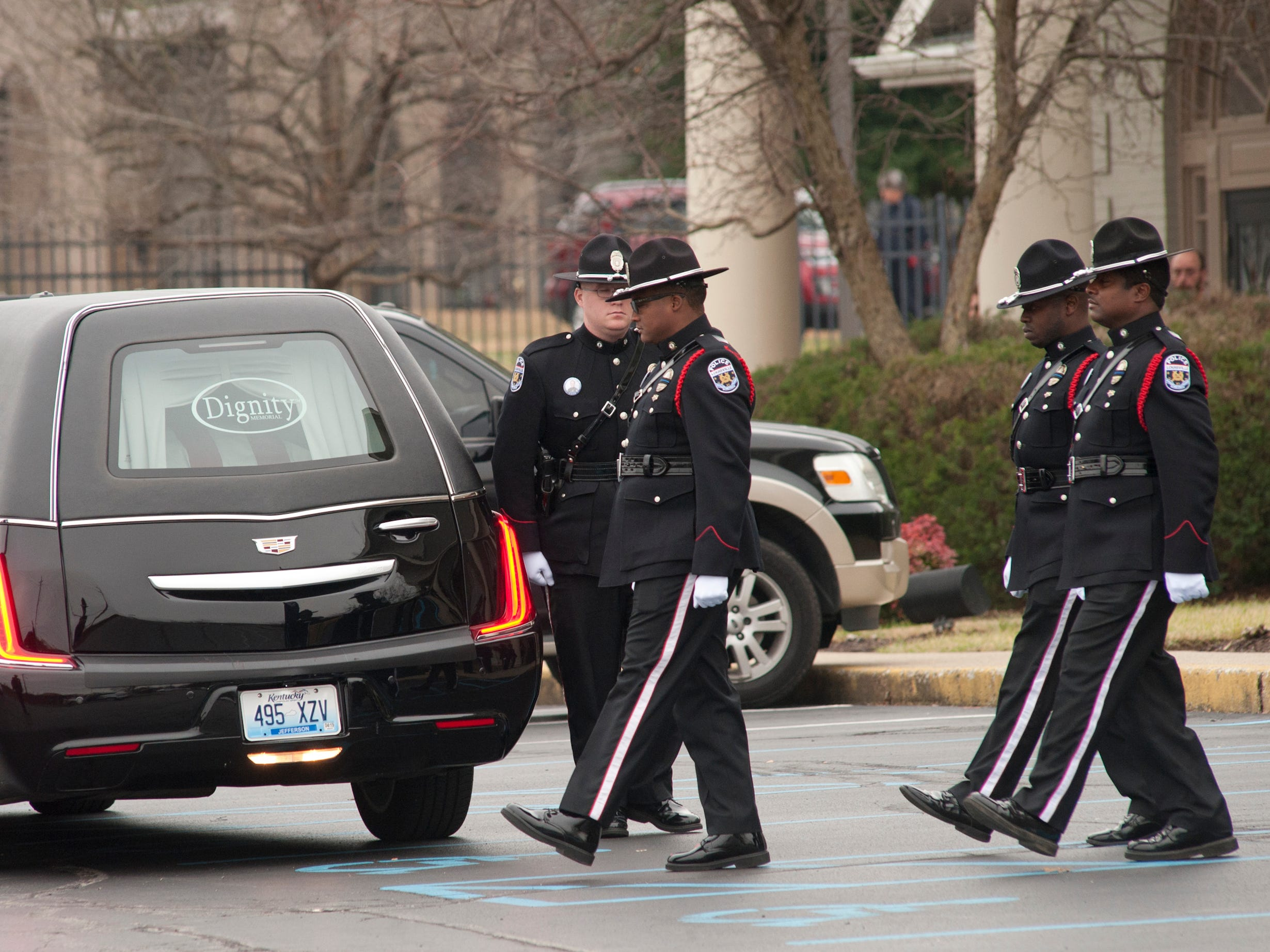 The LMPD Honor Guard slowly moves toward the hearse containing the casket of LMPD Detective Deidre Mengedoht in front of the Resthaven Funeral Home on Bardstown Road.