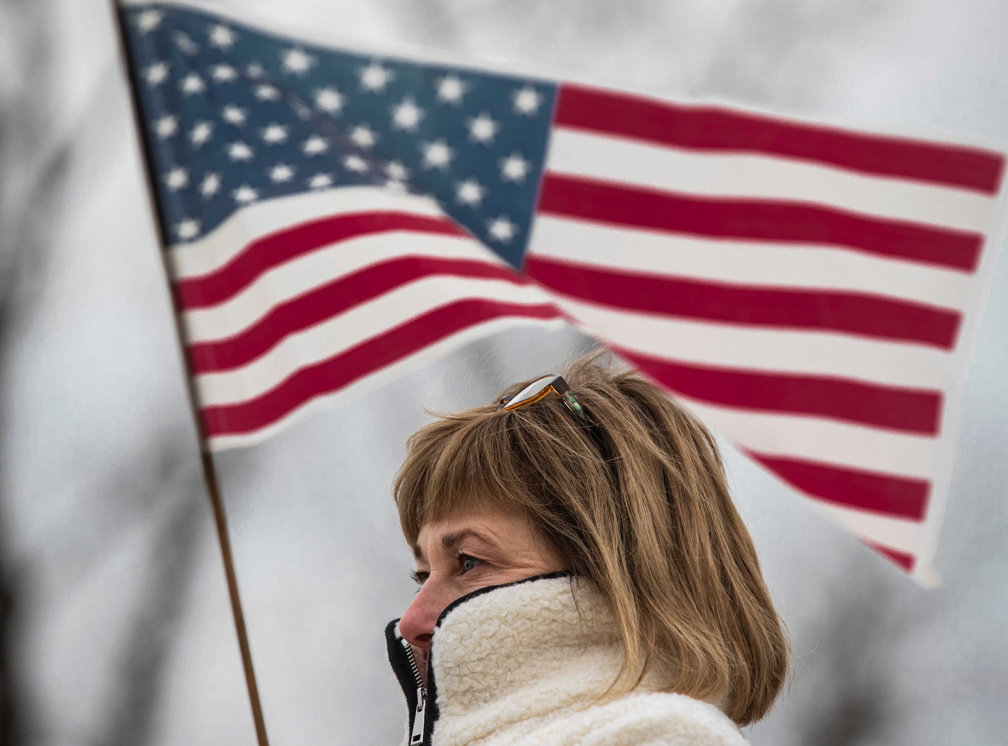 Karen Barnett holds a flag awaiting the procession of Det. Deidre Mengedoht as it reaches the Resthaven Funeral Home on Bardstown Road in Louisville, Ky. December 29, 2018