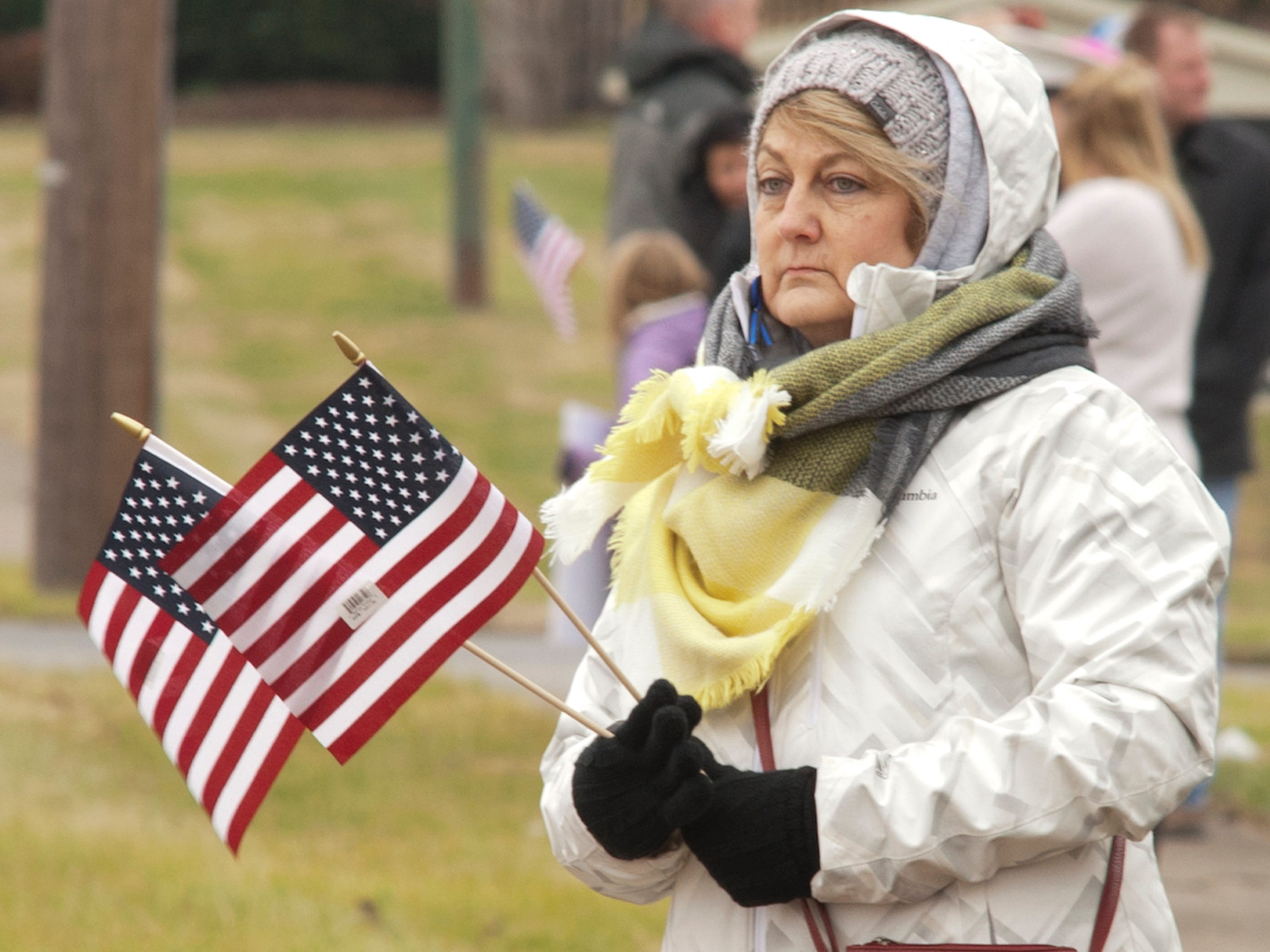 Vicki Yates of Hikes Point awaits the procession of LMPD Detective Deidre Mengedoht as it turns onto Bardstown Road. Yates gave out U.S. flags to others on the street who had come out to pay their respects to Mengedoht. Yates' daughter, Allison Grider, trained in the same cadet class as Mengedoht, and Yates' daughter and son both serve in LMPD's 7th Division. 29 December 2018