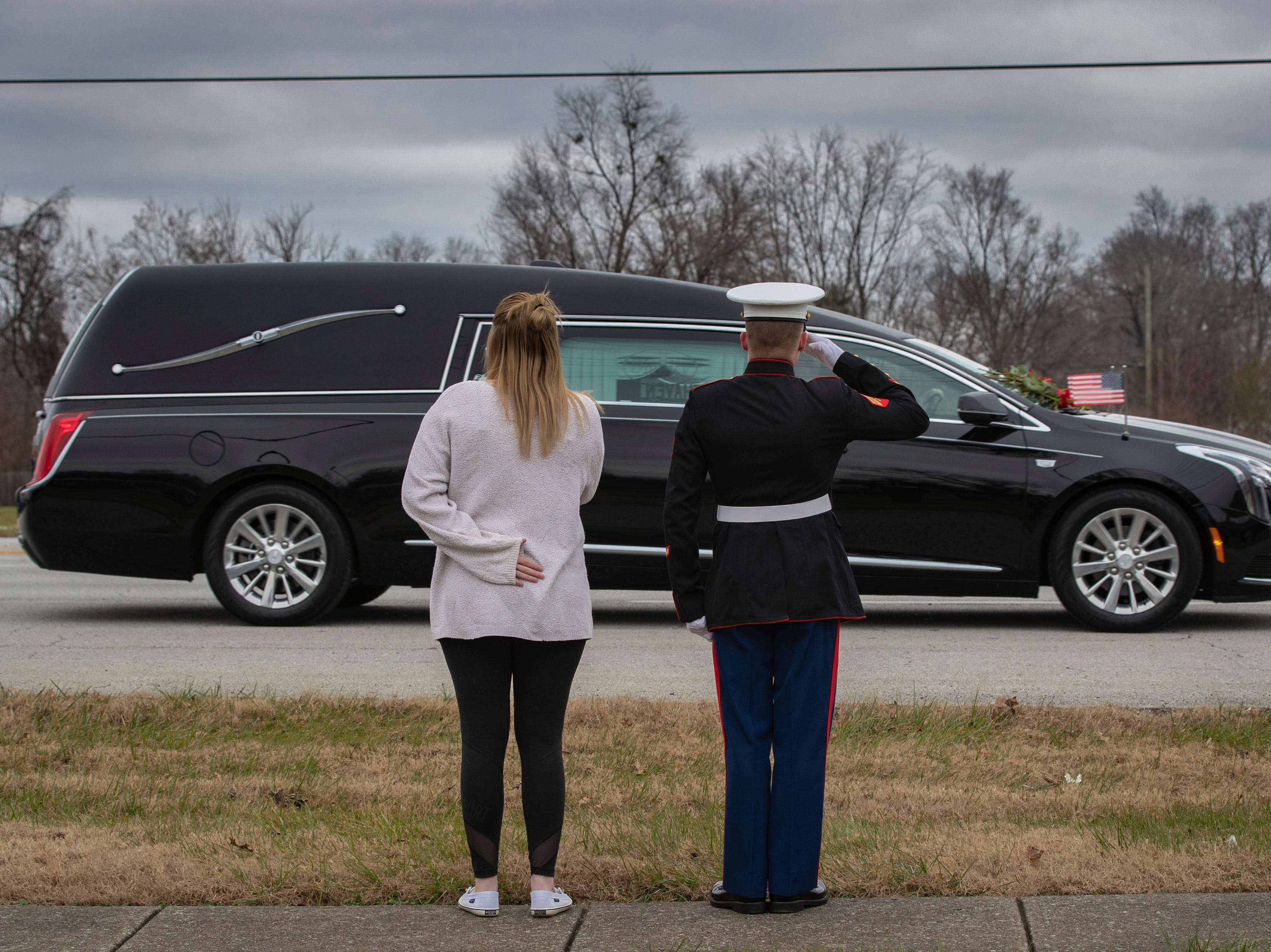 A military officer salutes as the hearse carrying Deidre Mengedoht passes by heading to the Resthaven Funeral Home on Bardstown Road in Louisville, Ky. December 29, 2018