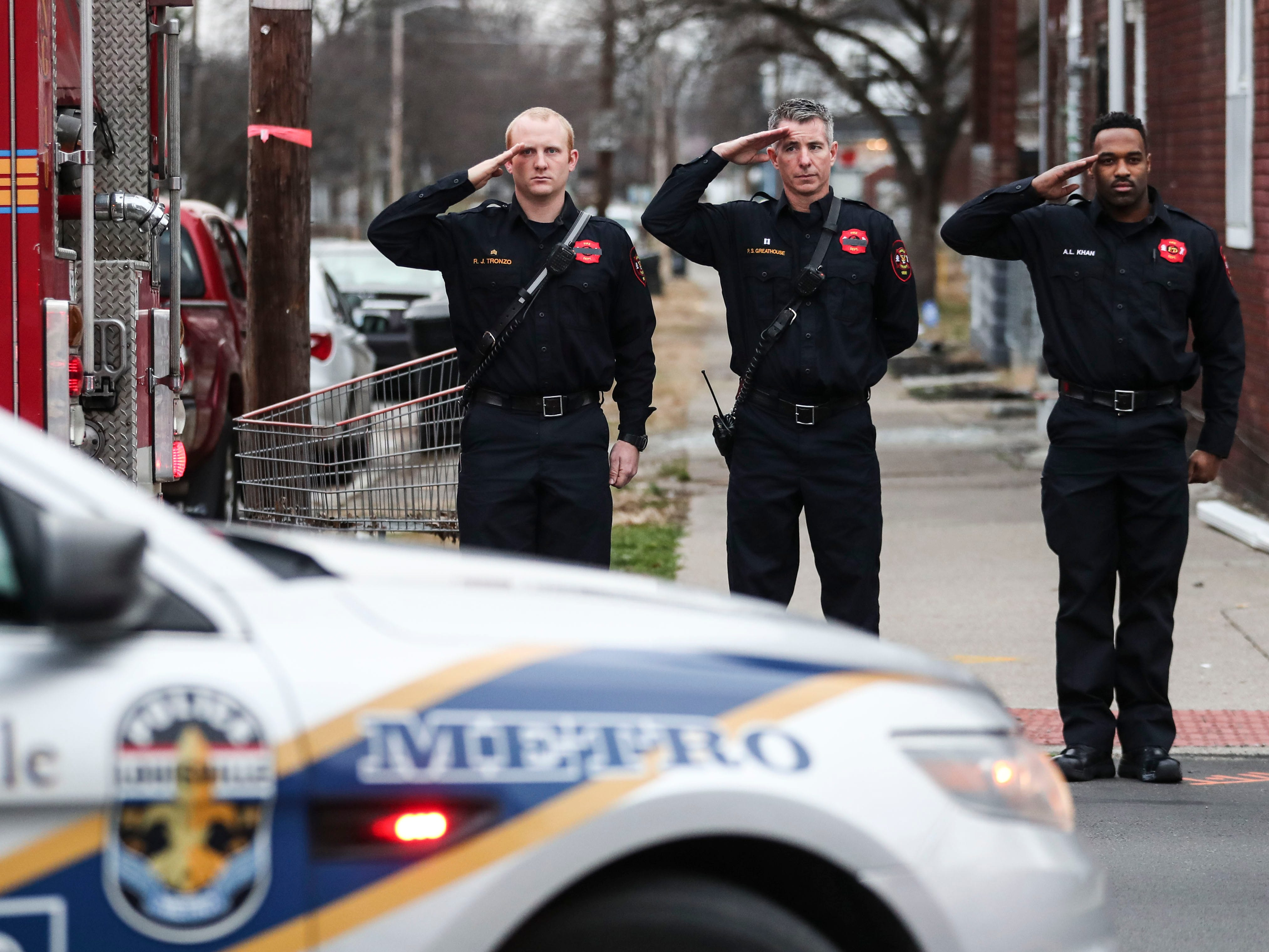 Louisville firefighters salute as the procession for LMPD Detective Deidre Mengedoht proceeds north on 4th Street as part of her last tour through the neighborhoods she patrolled as well as the Second District headquarters. Dec. 29, 2018