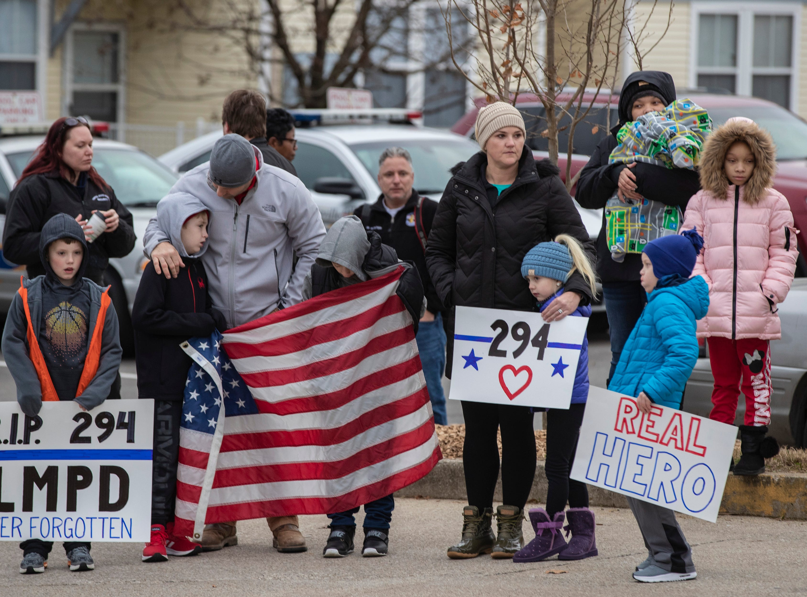 Jake Bibb, from left, stands with Brady Lauder, Brady's father, LMPD Det. Mike Lauder, Thomas Evans, Julie Lauder, Caroline Lauder and Chase Bibb during the procession of Det. Deidre Mengedoht as it stops at the 2nd Division headquarters in Park DuValle. December 29, 2018