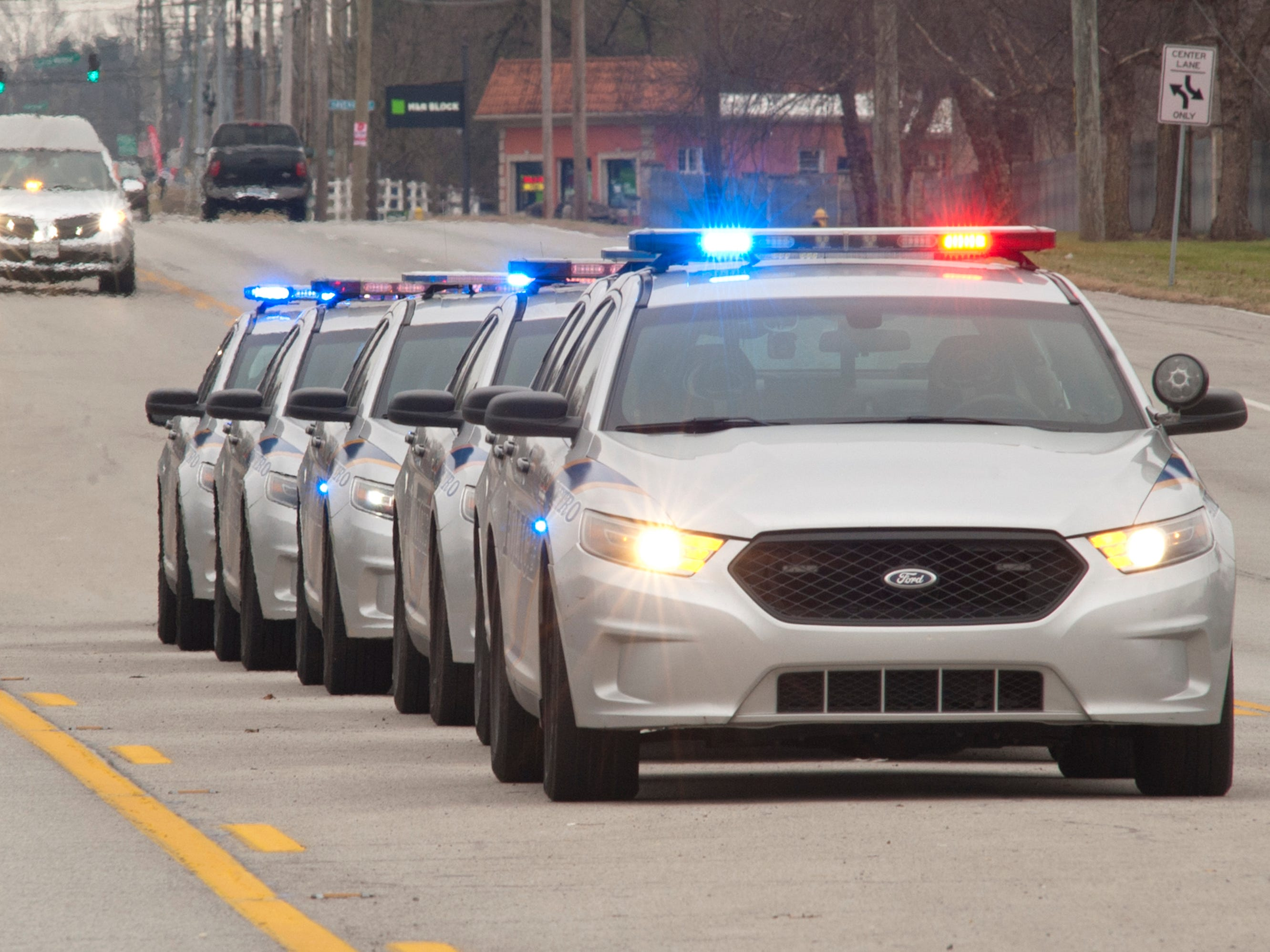 LMPD police cars line up in the center lane of Bardstown Road as the officers await the procession of LMPD Detective Deidre Mengedoht from S. 3rd Street to the Resthaven Funeral Home.