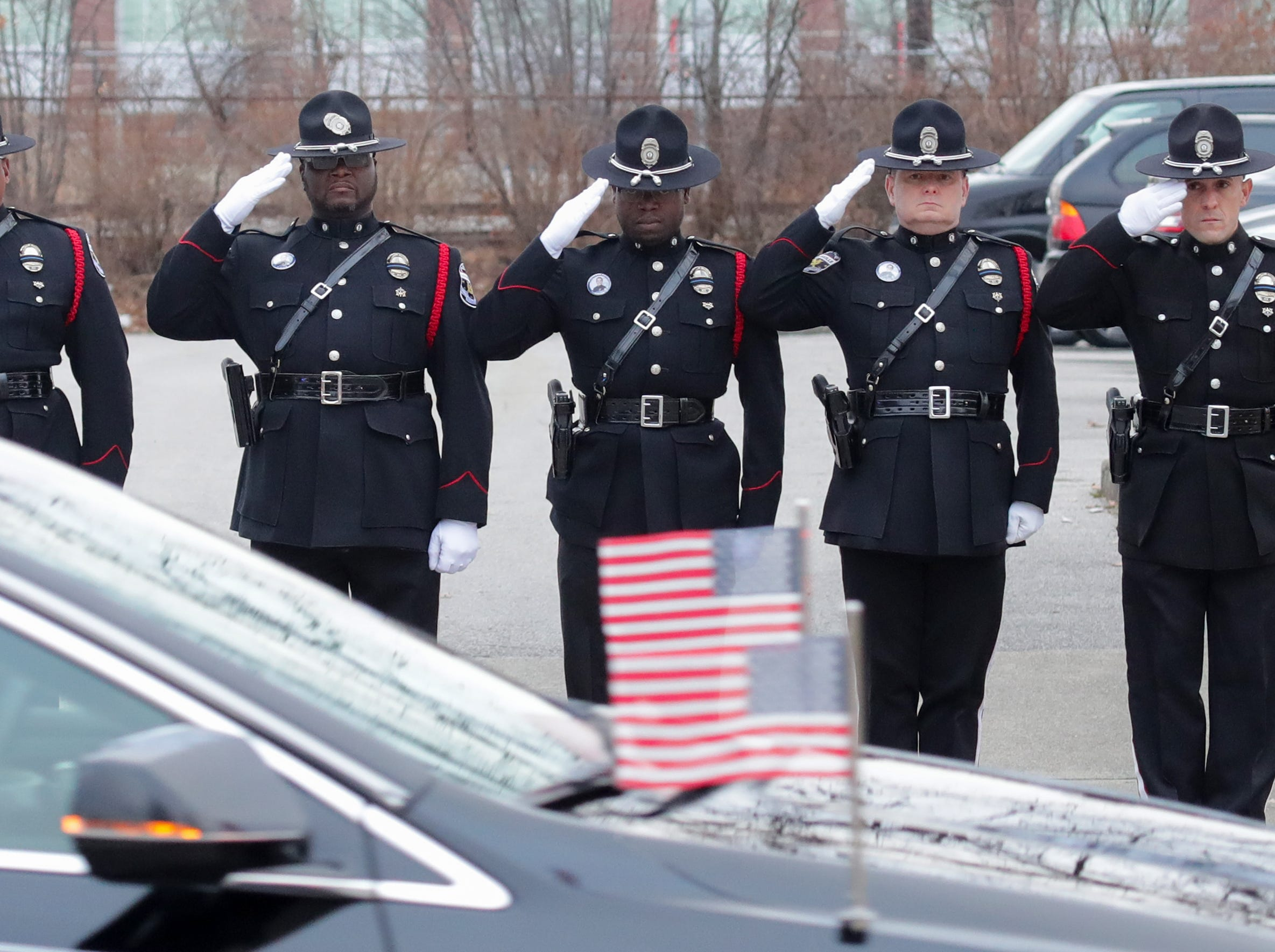 Louisville Metro Police salute as procession leaves the O.D. White Funeral home.