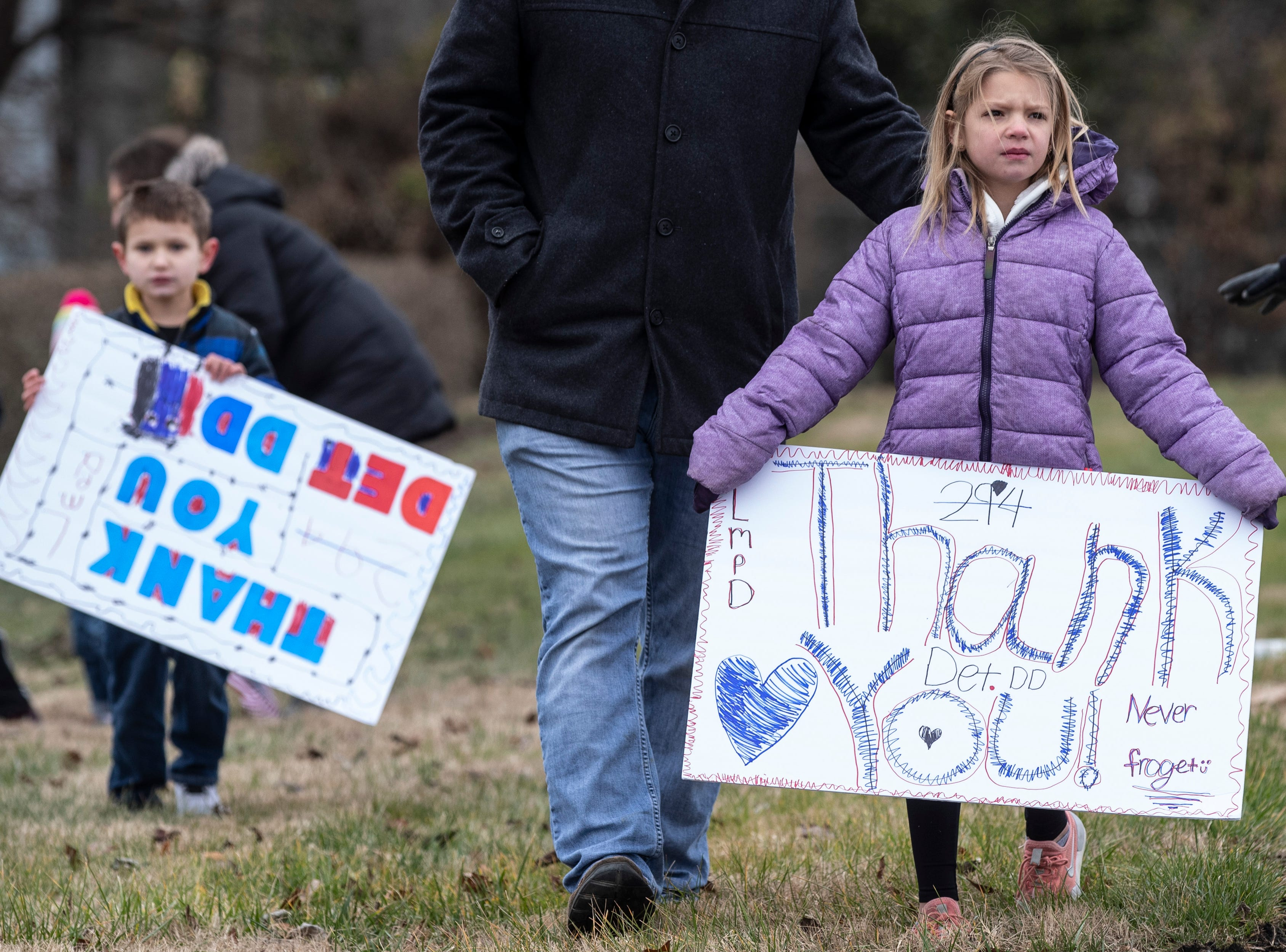 Children hold signs in honor of Det. Deidre Mengedoht along Bardstown Road on Saturday. December 29, 2018