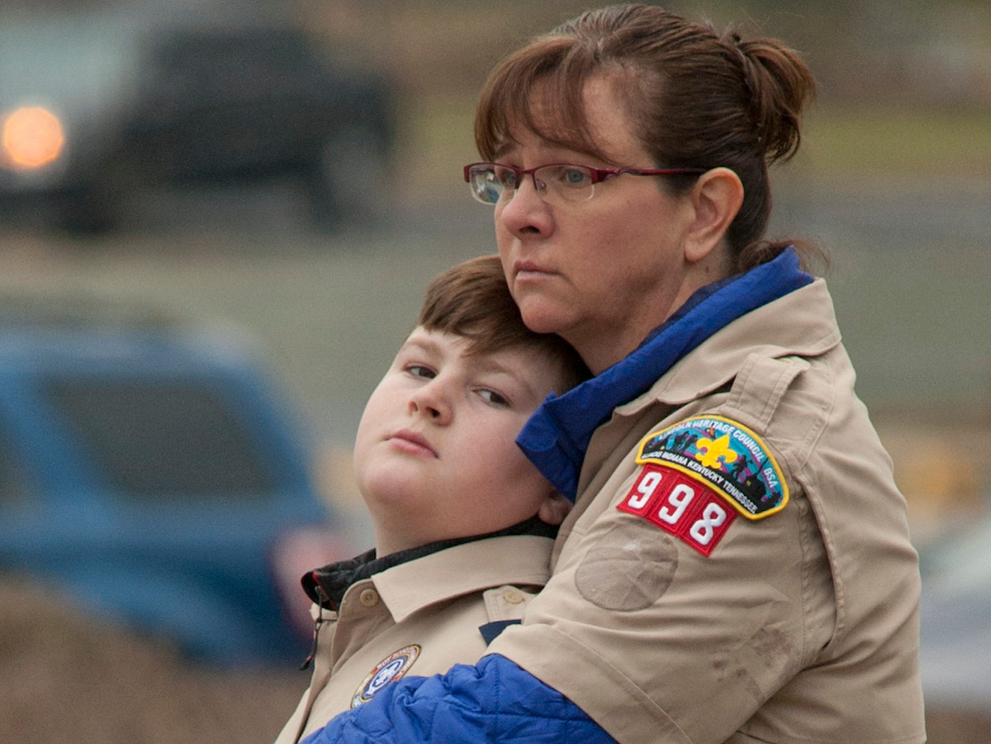 "Cub Scout Josh Wagner, 10, is clutched by his mother, Martha, as they watch the procession of LMPD Detective Deidre Mengedoht enter the Funeral Home on Bardstown Road. Josh is in the same scout pack (Pack 998) as Detective Mengedoht's son, Preston, age 9. ""We hope our presence helps Preston,"" she said. 29 December 2018"