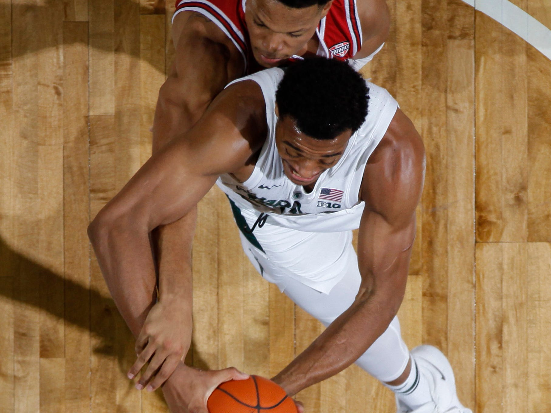 Michigan State's Xavier Tillman, bottom, is fouled by Northern Illinois' Lacey James, Saturday, Dec. 29, 2018, in East Lansing, Mich.
