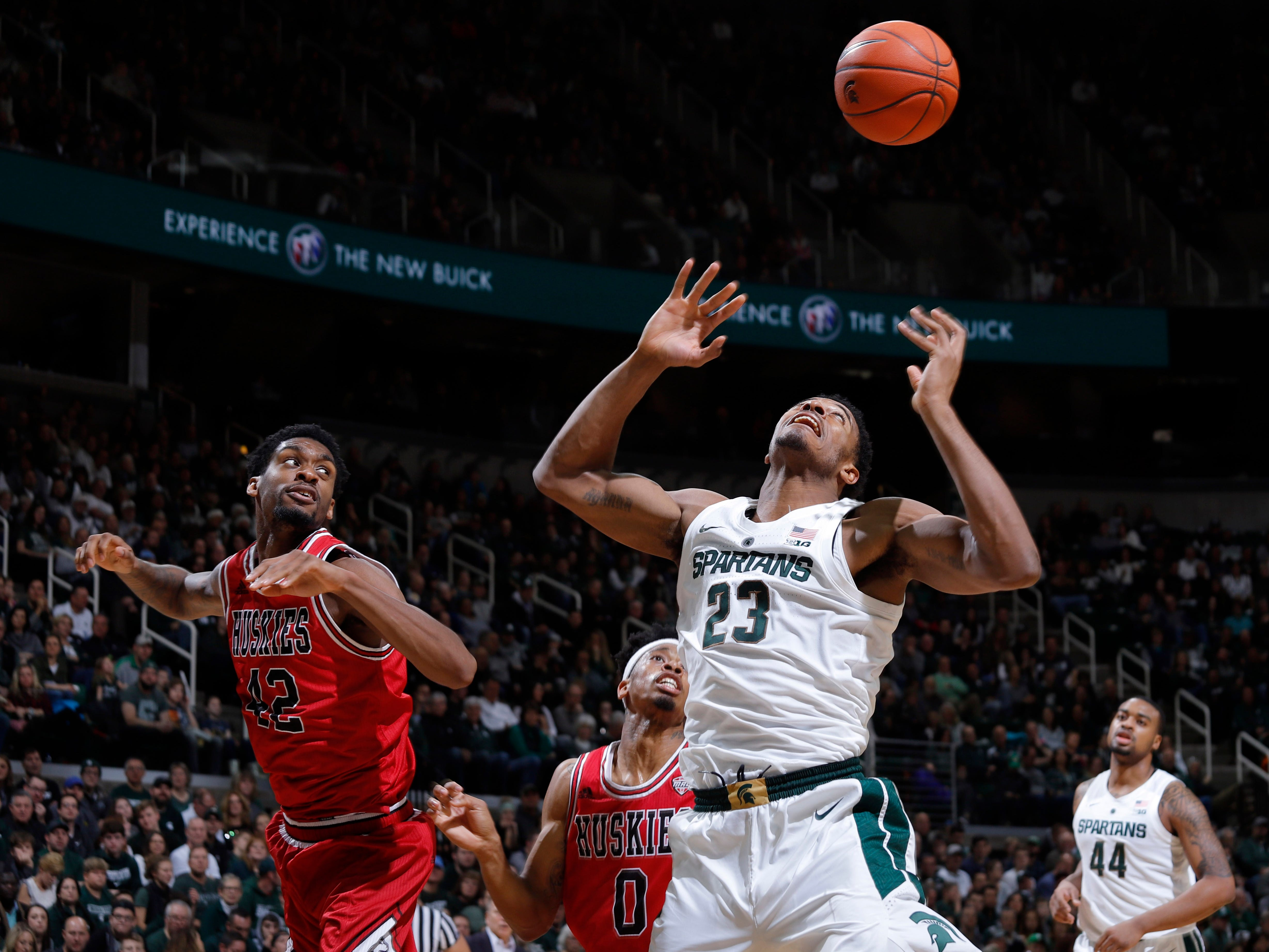 Michigan State's Xavier Tillman (23) and Northern Illinois' Levi Bradley, left, and Dante Thorpe (0) reach for a rebound, Saturday, Dec. 29, 2018, in East Lansing, Mich.