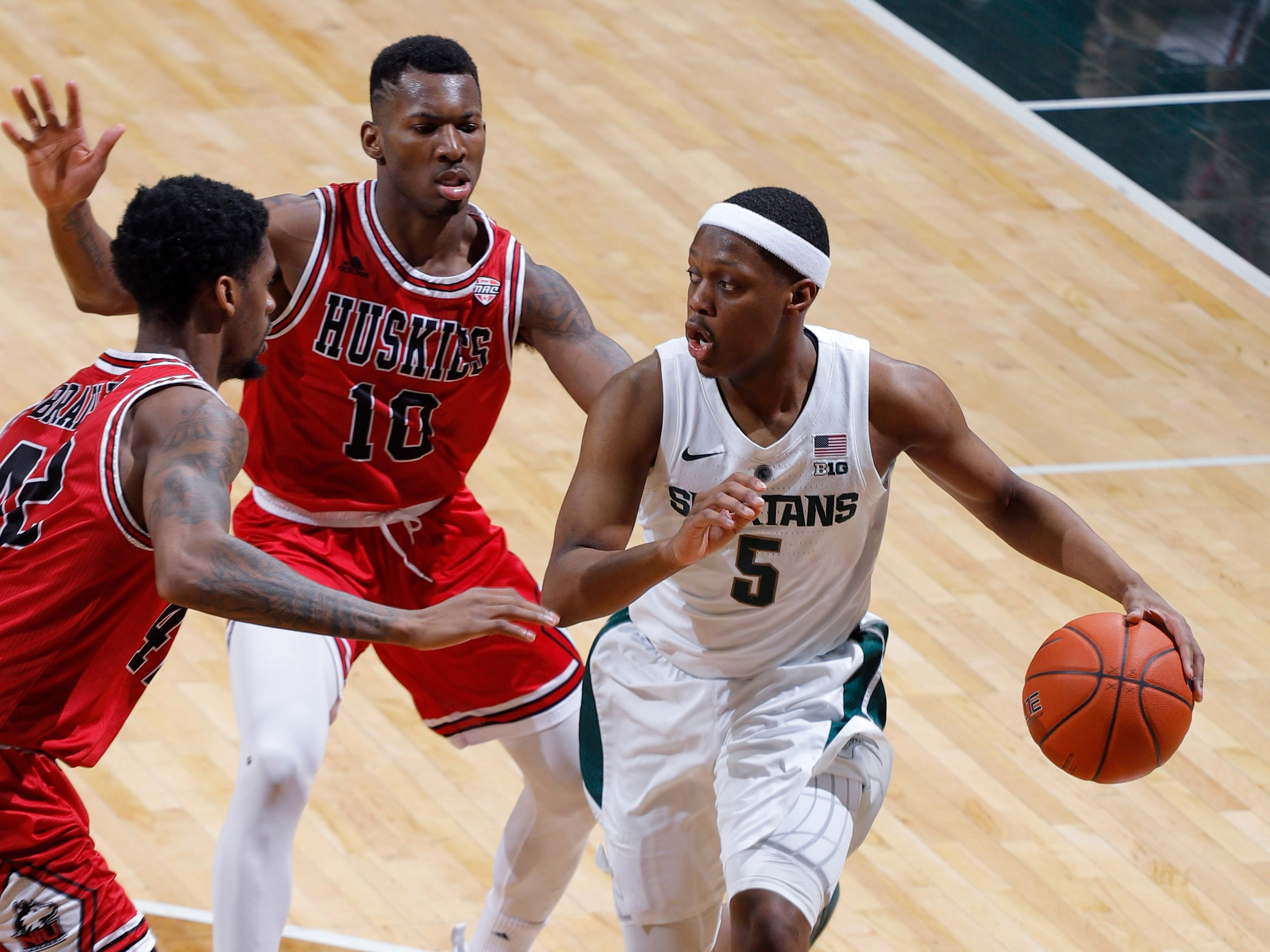 Michigan State's Cassius Winston, right, controls the ball against Northern Illinois' Eugene German, center, and Levi Bradley, Saturday, Dec. 29, 2018, in East Lansing, Mich.
