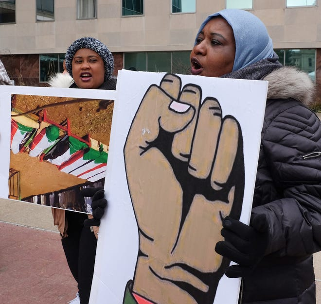 Sadia Hassan, left, from Lansing, and Intasar Elseddig, from Canton, attend a protest to bring attention to the recent violence in Sudan at Lansing's City Hall Saturday, Dec. 29, 2018. Over 50 people attended the rally.