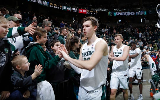 Michigan State players, including Matt McQuaid, from left, Thomas Kithier and Gabe Brown greet fans following their game against Northern Illinois, Saturday, Dec. 29, 2018, in East Lansing, Mich.