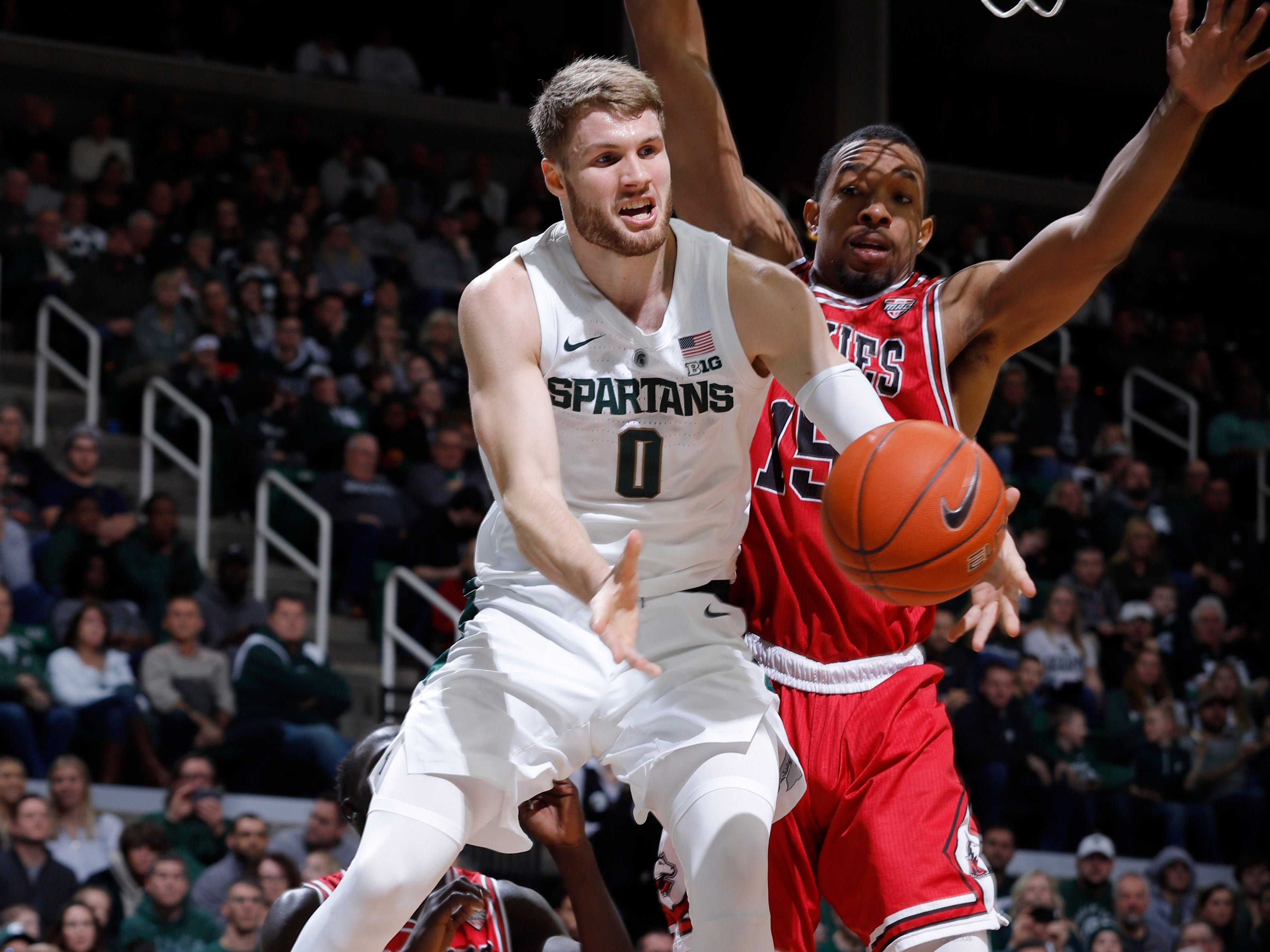 Michigan State's Kyle Ahrens (0) dishes off under the basket against Northern Illinois' Jaylen Key, Saturday, Dec. 29, 2018, in East Lansing, Mich.