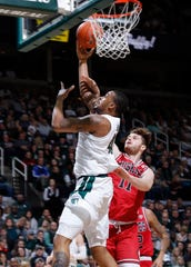 Michigan State's Nick Ward, left, is fouled on a shot by Northern Illinois' Noah McCarty, Saturday, Dec. 29, 2018, in East Lansing, Mich.