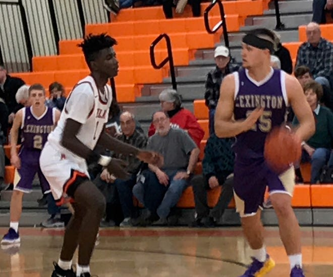 Ashland's Klejhan Randleman defends against Lexington's Cade Stover in Friday's Ohio Cardinal Conference basketball game.