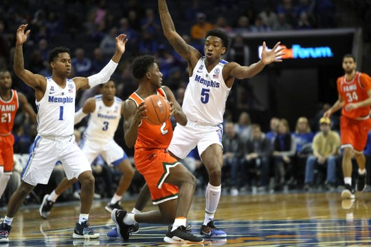 Memphis Tigers guards Tyler Harris, left, and Kareem Brewton Jr. defend Florida A&M Rattlers guard  Kamron Reaves during their game at the FedExForum on Saturday, Dec. 29, 2018.