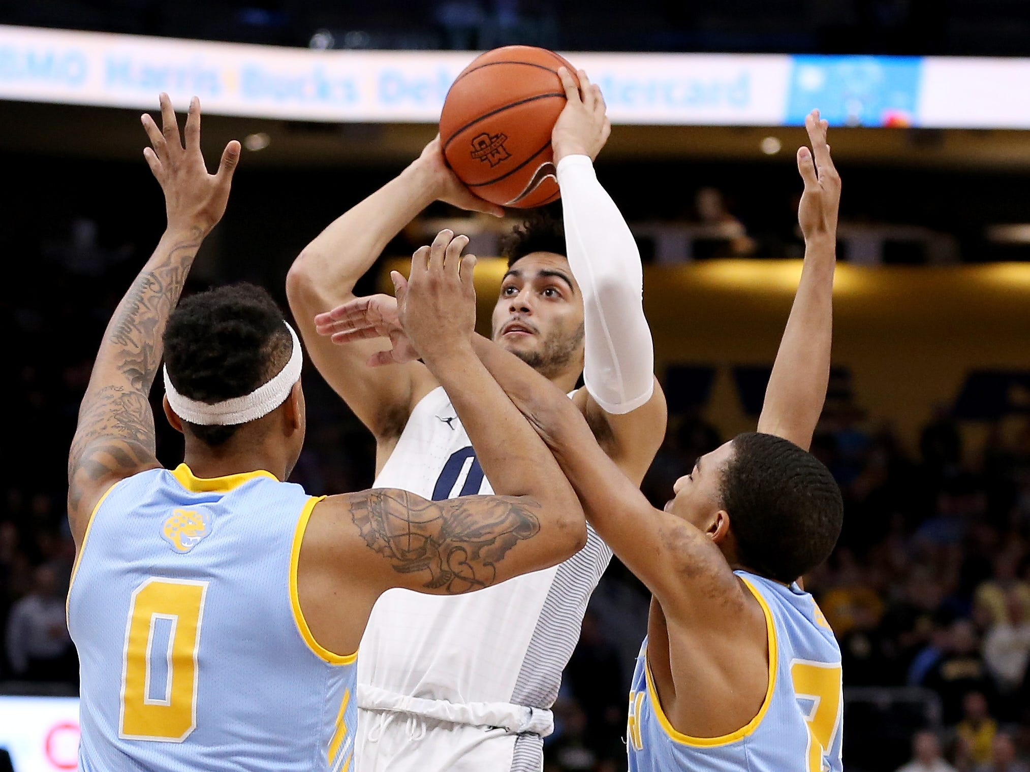 Markus Howard of Marquette puts up a shot over a pair of Southern defenders during the the first half when he scored 23 of his 26 points Friday night.