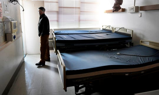 Mayor of Ducktown Mayor Doug Collins stands in the doorway of a room wehre hosptial beds have been stored inside town's shuttered hospital in Ducktown, Tennessee on Dec. 5, 2018. Copper Basin Medical Center closed 15 months ago due to mounting debt.