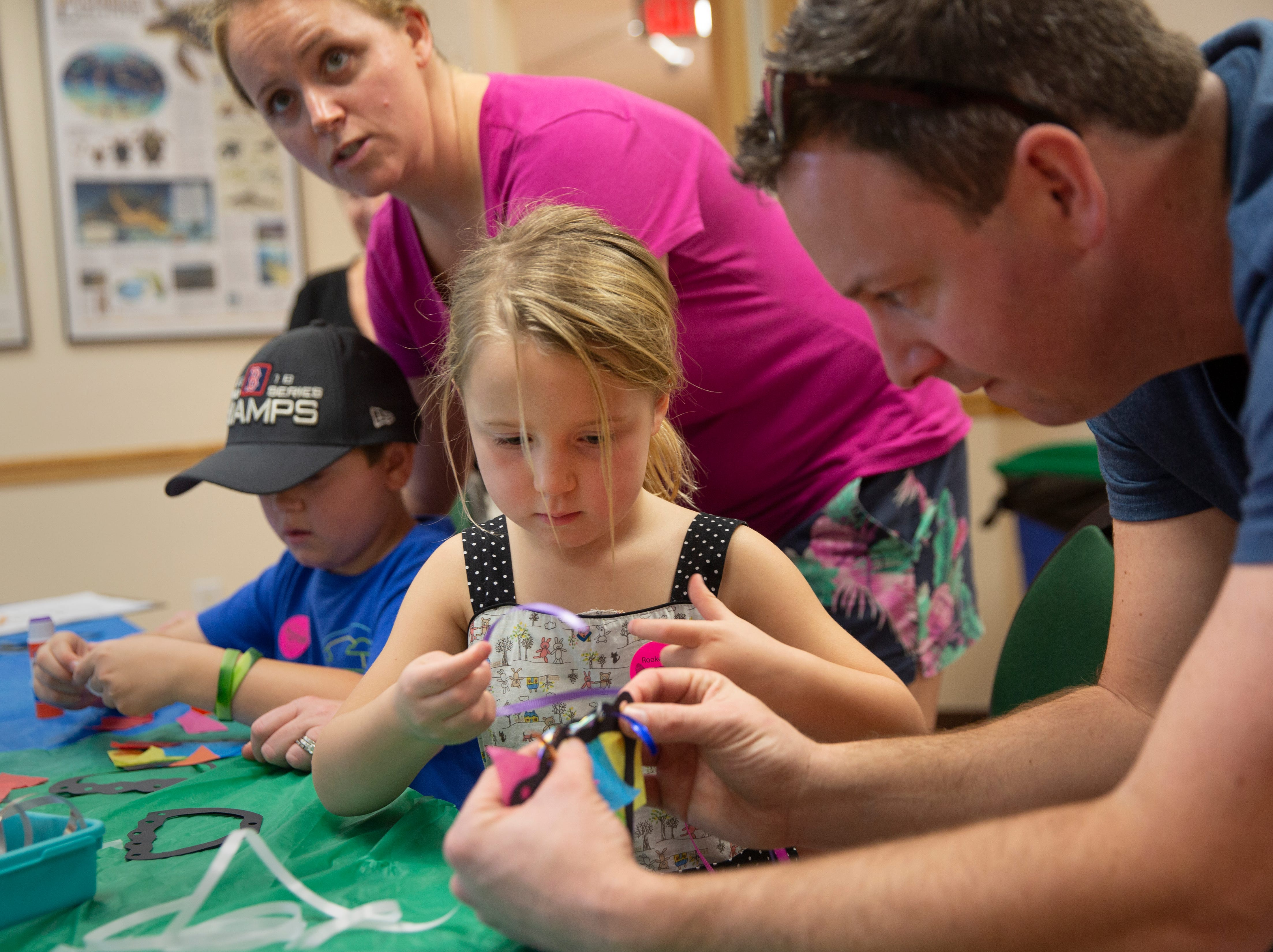 The Gillespie family, from left, son Jack Gillespie, mom Cristin Gillespie, daughter Eleanor Gillespie and dad Sean Gillespie work on a craft project during the Rookery Bay Environmental Learning Center's Science Saturday, Dec. 29, 2018 south of Naples.