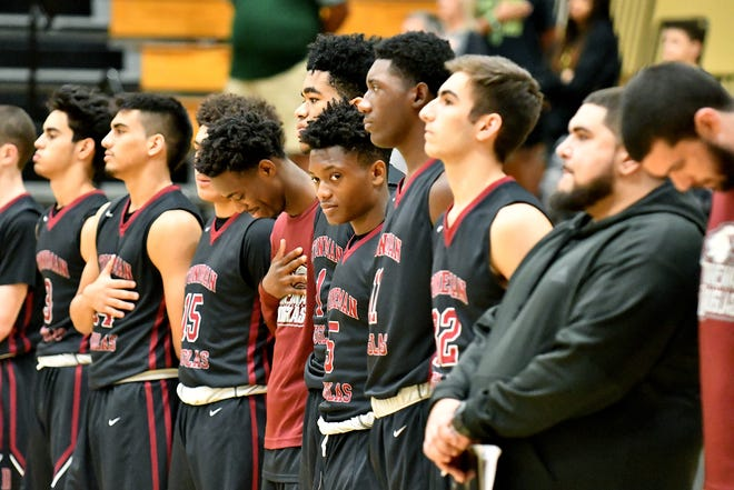 Stoneman Douglas High School basketball players during the national anthem before their game with Golden Gate High School during the Kelleher Firm Gulfshore Holiday Hoopfest on Thursday.