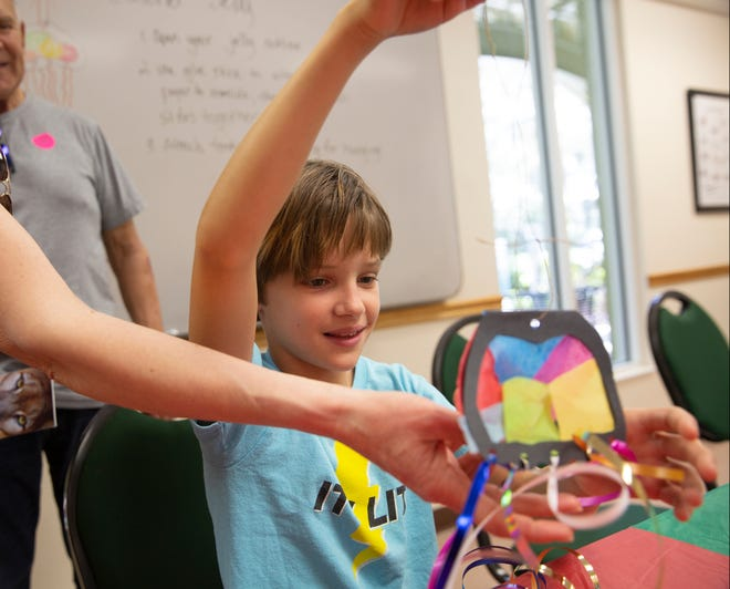 Malia Valentic of Culver City, California, admires the jelly fish she made during Science Saturday at the Rookery Bay Environmental Learning Center, Saturday, Dec. 29, 2018 south of Naples.