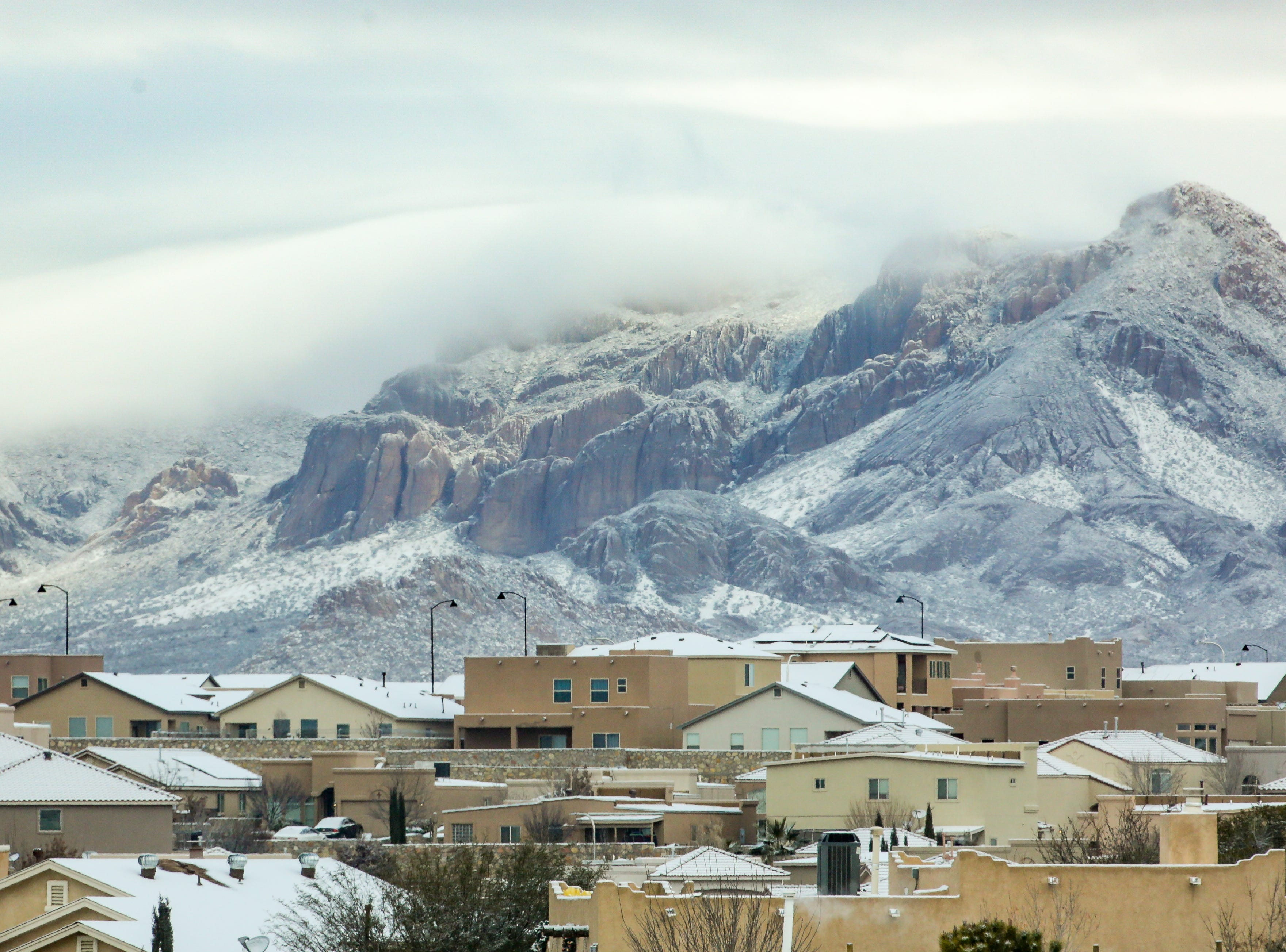 Rooftops are covered with snow as the Doña Ana Mountains are pictured in the background on Saturday Dec. 29, 2019.