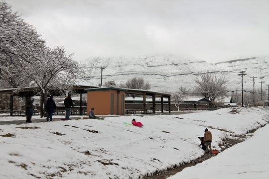 Visitors to Washington Park sled into the park's arroyo SAturday.