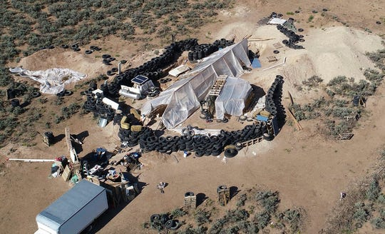 This Aug. 10, 2018, file photo shows a ramshackle compound in the desert area of Amalia, N.M. Five former residents of the compound in northern New Mexico, where a 3-year-old boy's body was found in July, were scheduled to appear in federal court on firearms-related charges. A hearing on Sept. 4 focused on allegations against Jany Leveille of illegal possession of firearms and ammunition linked to her unlawful immigration status and conspiracy accusations against the four other defendants.