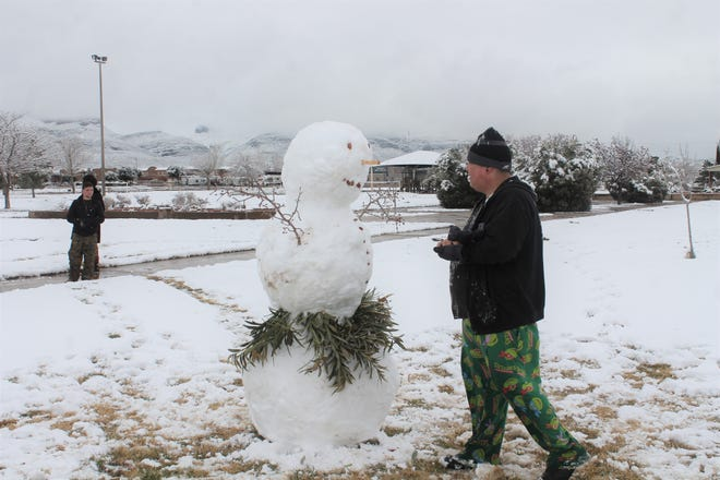 Ryan Silva puts the finishing touches on a snowman at Washington Park Saturday.