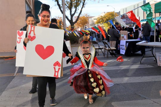"Kristin Seibel, dressed as a member of the card army in ""Alice in Wonderland,"" and Annabelle Seibel, dressed as the Queen of Hearts, walk down a crosswalk along Main Street during BooPalooza Oct. 31 in Farmington."
