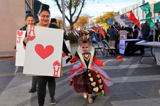 """Kristin Seibel, dressed as a member of the card army in """"Alice in Wonderland,"""" and Annabelle Seibel, dressed as the Queen of Hearts, walk down a crosswalk along Main Street during BooPalooza Oct. 31 in Farmington."""