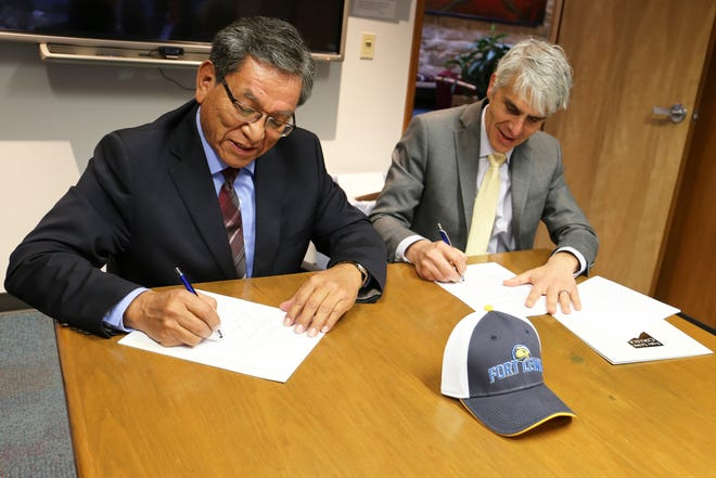 Navajo Nation President Russell Begaye, left, and Fort Lewis College President Tom Stritikus sign an agreement on Thursday in Durango, Colo.