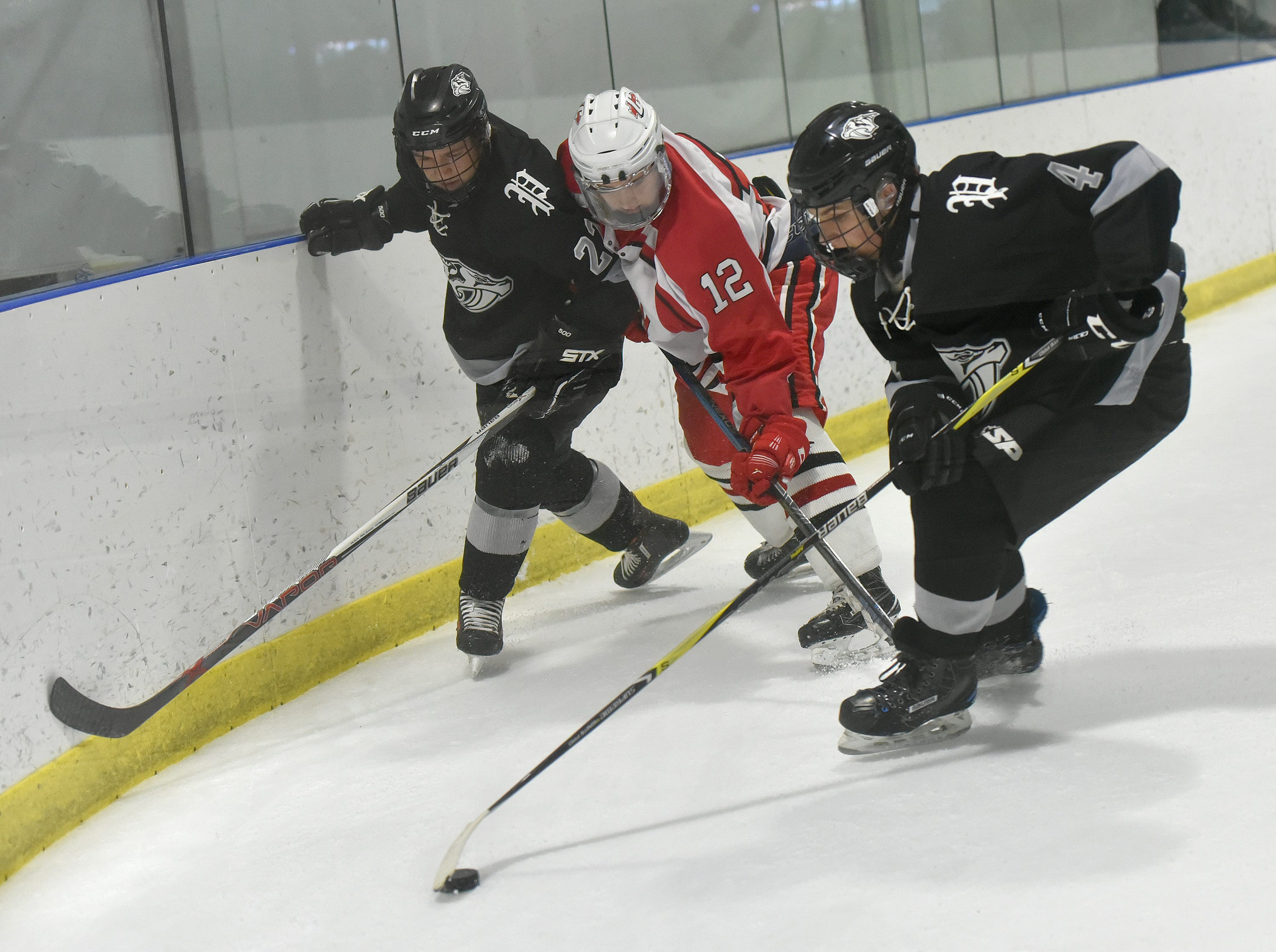 Widcats Brendan Matey (4) and Nick Schoen (22) pull the puck from the corner, away from Chief James Monteith (12).