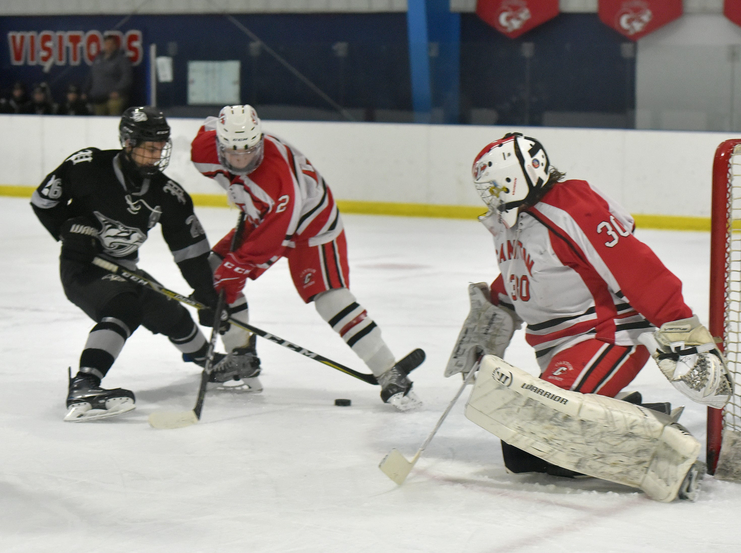 Plymouth's Jack VanDenBeurgeury skates to the net and shoots under pressure from Chief defender Tyler Laski (2), but Canton goalie Michael Renzi (30) makes the save.