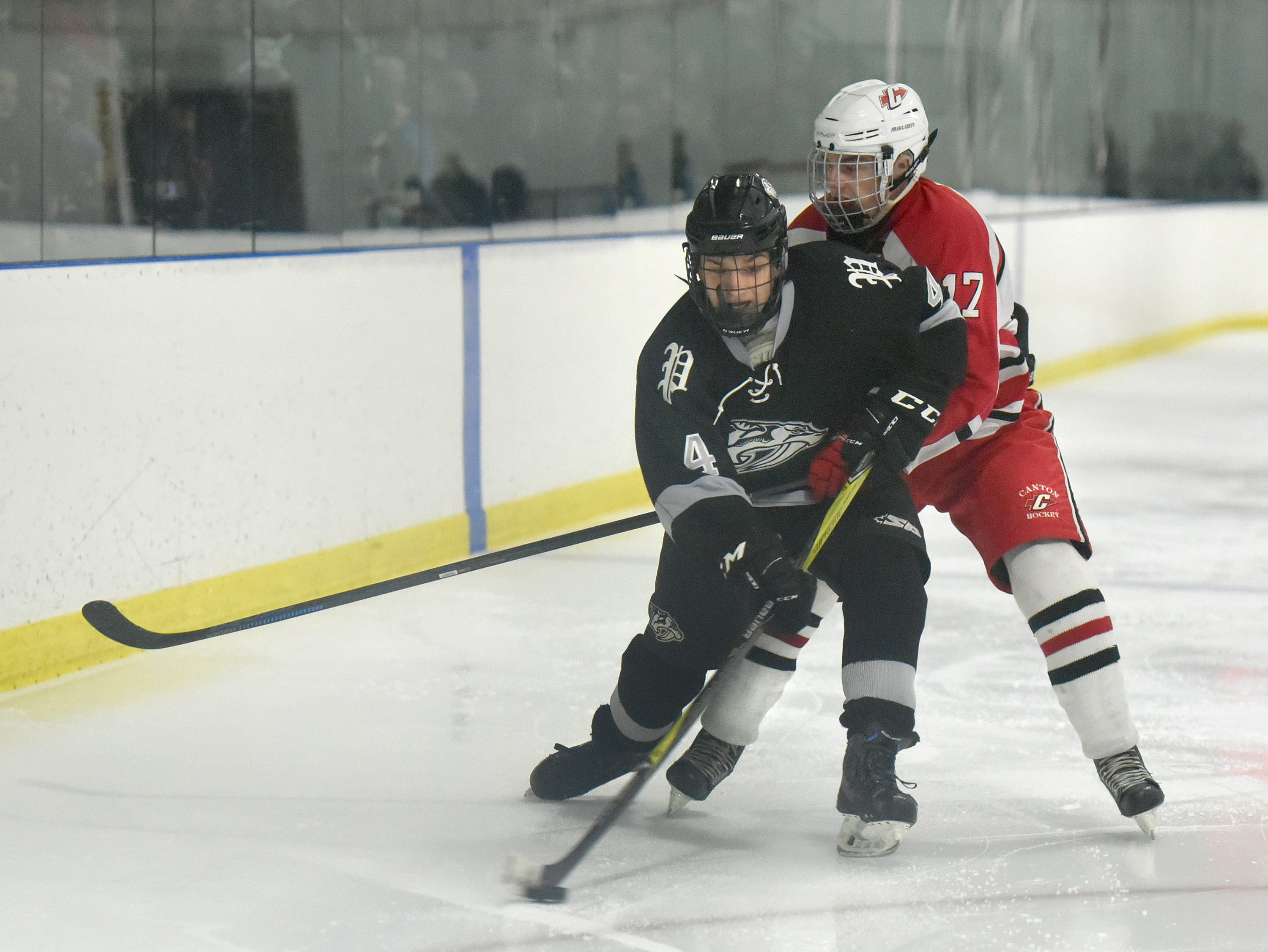Wildcat Brendan Matey (4) has the puck, with Chief Declan O'Hare on his tail.