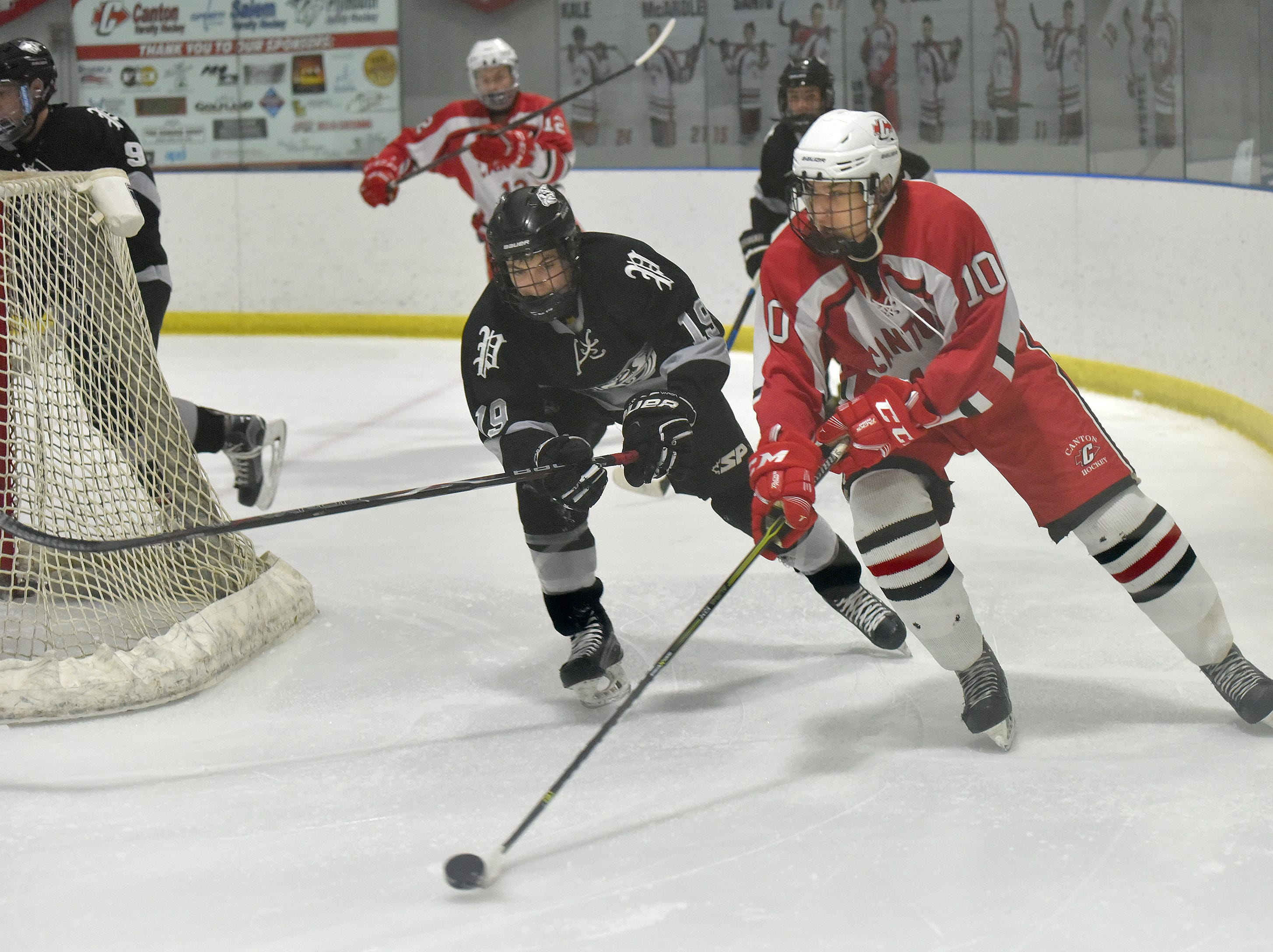 Chief defender Hadley Hudak (10) and Plymouth's Gavin Roach, behind the Canton net.