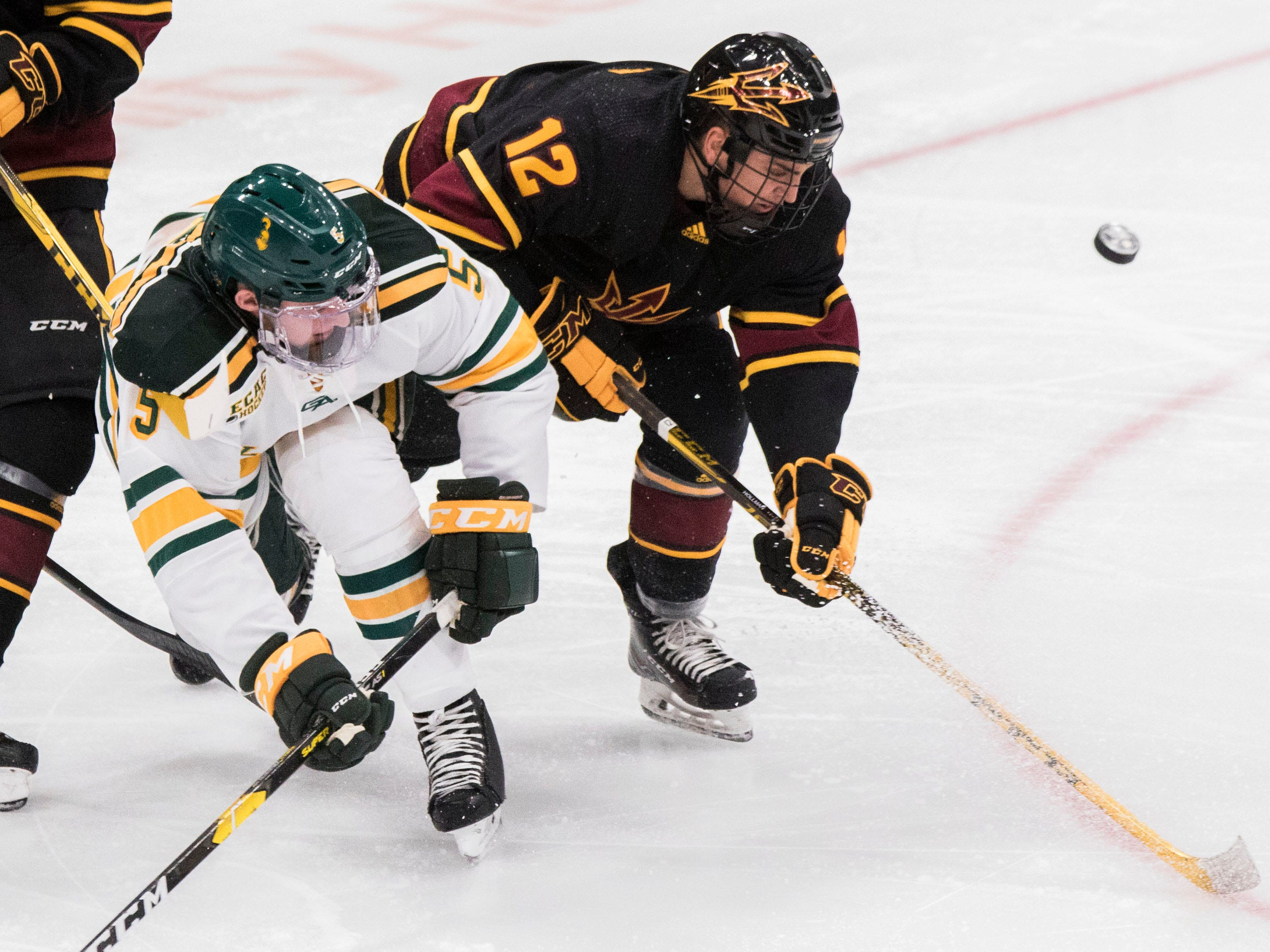 Arizona State University's Dylan Hollman (12) goes for the puck against Clarkson's Michael Underwood (5) during the first period of their game in the 2018 Desert Hockey Classic in Glendale, Friday, Dec. 28, 2018.