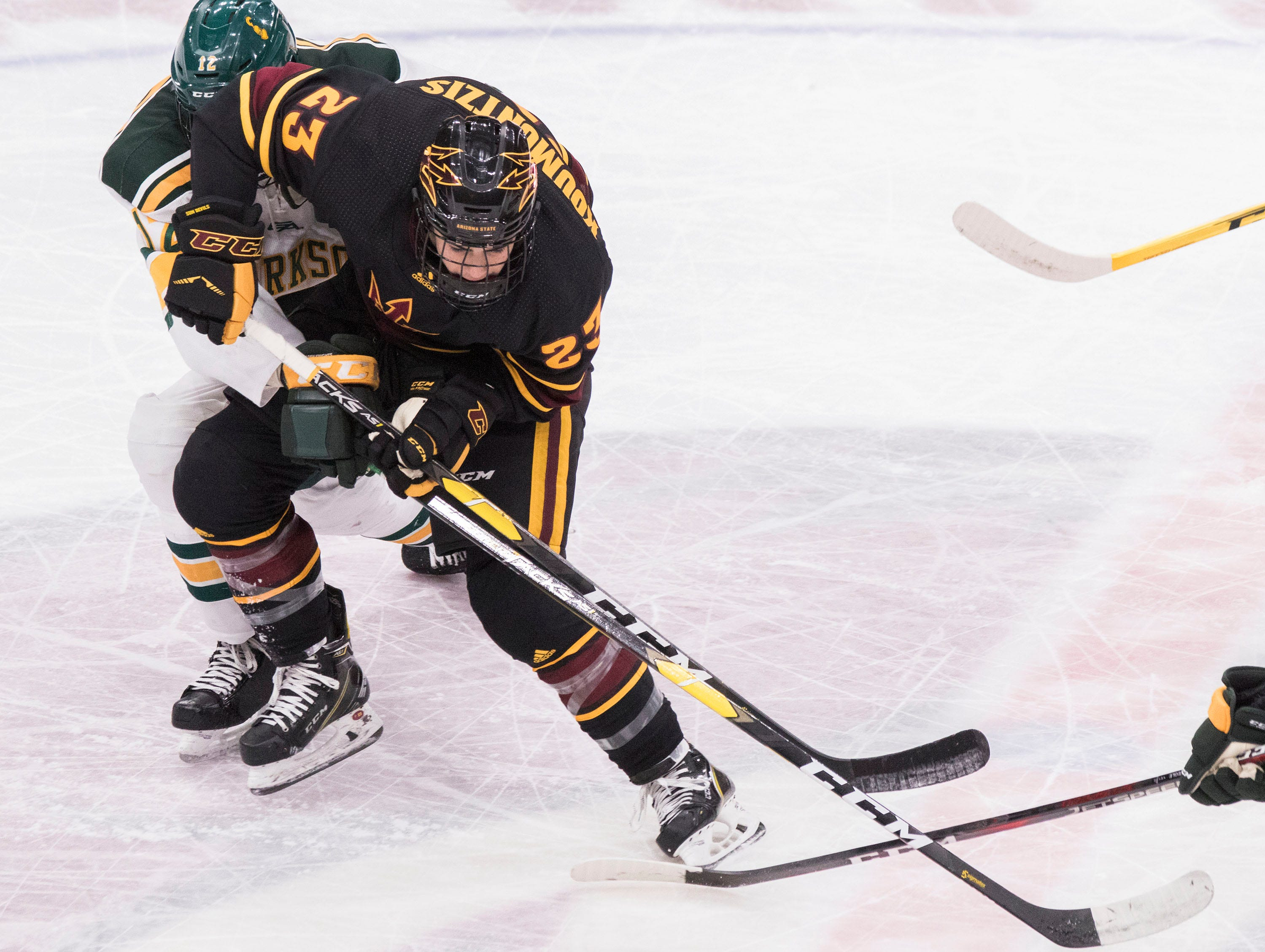 Arizona State University's Demetrios Koumontzis (23) battles for the puck against Clarkson's Jordan Schneider (12) during the first period of their game in the 2018 Desert Hockey Classic in Glendale, Friday, Dec. 28, 2018.