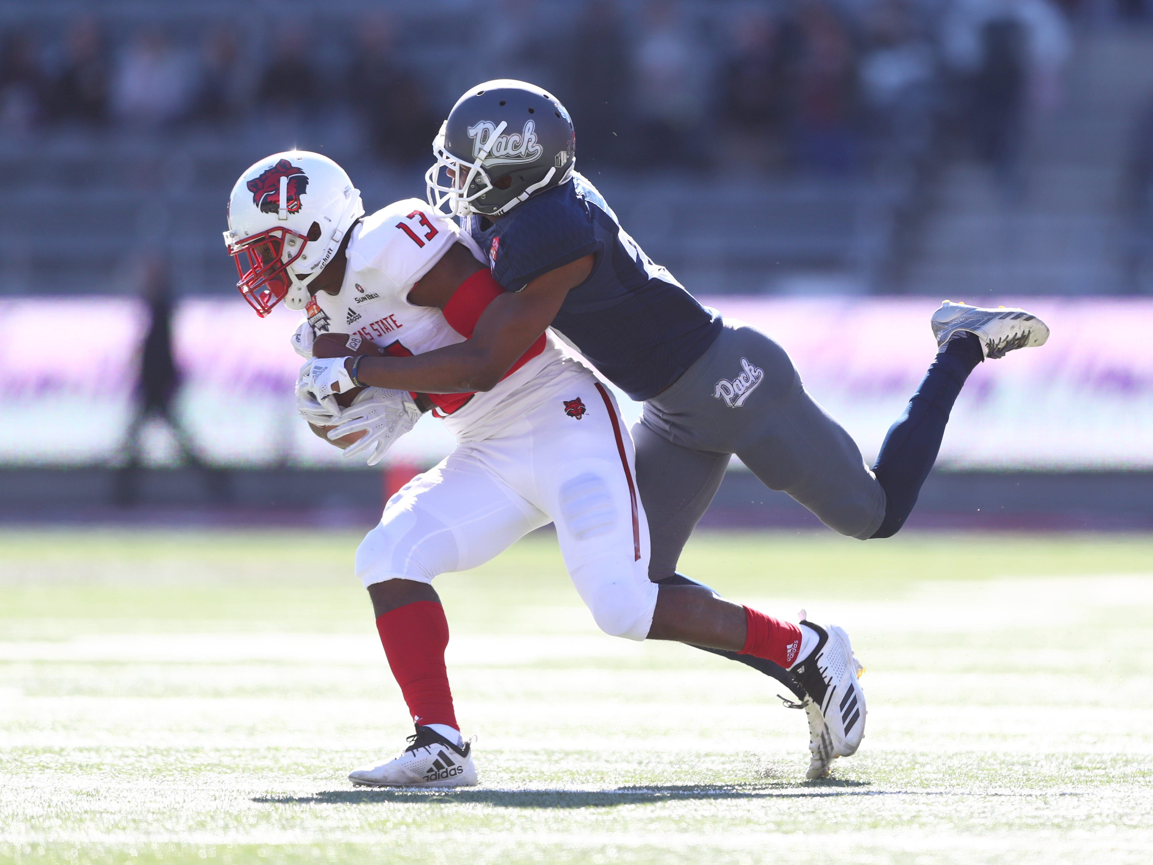 Dec 29, 2018; Tucson, AZ, USA; Arkansas State Red Wolves wide receiver Kirk Merritt (13) is tackled by Nevada Wolf Pack defensive back Daniel Brown (25) in the first half of the 2018 Arizona Bowl at Arizona Stadium.