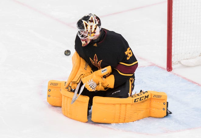 Arizona State University goalie Joey Daccord (35) deflects the puck against Clarkson during the first period of their game in the 2018 Desert Hockey Classic in Glendale, Friday, Dec. 28, 2018.