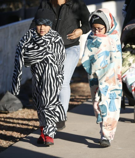 Analise Sanchez, 7, (L) and her cousin Anaya Hernandez, 7, curl up in blankets to avoid the cold during the Fiesta Bowl Parade in Phoenix on Dec.  29, 2018.