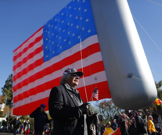 A giant inflatable American flag comes down Central Avenue during the Fiesta Bowl Parade in Phoenix on Dec. 29, 2018.