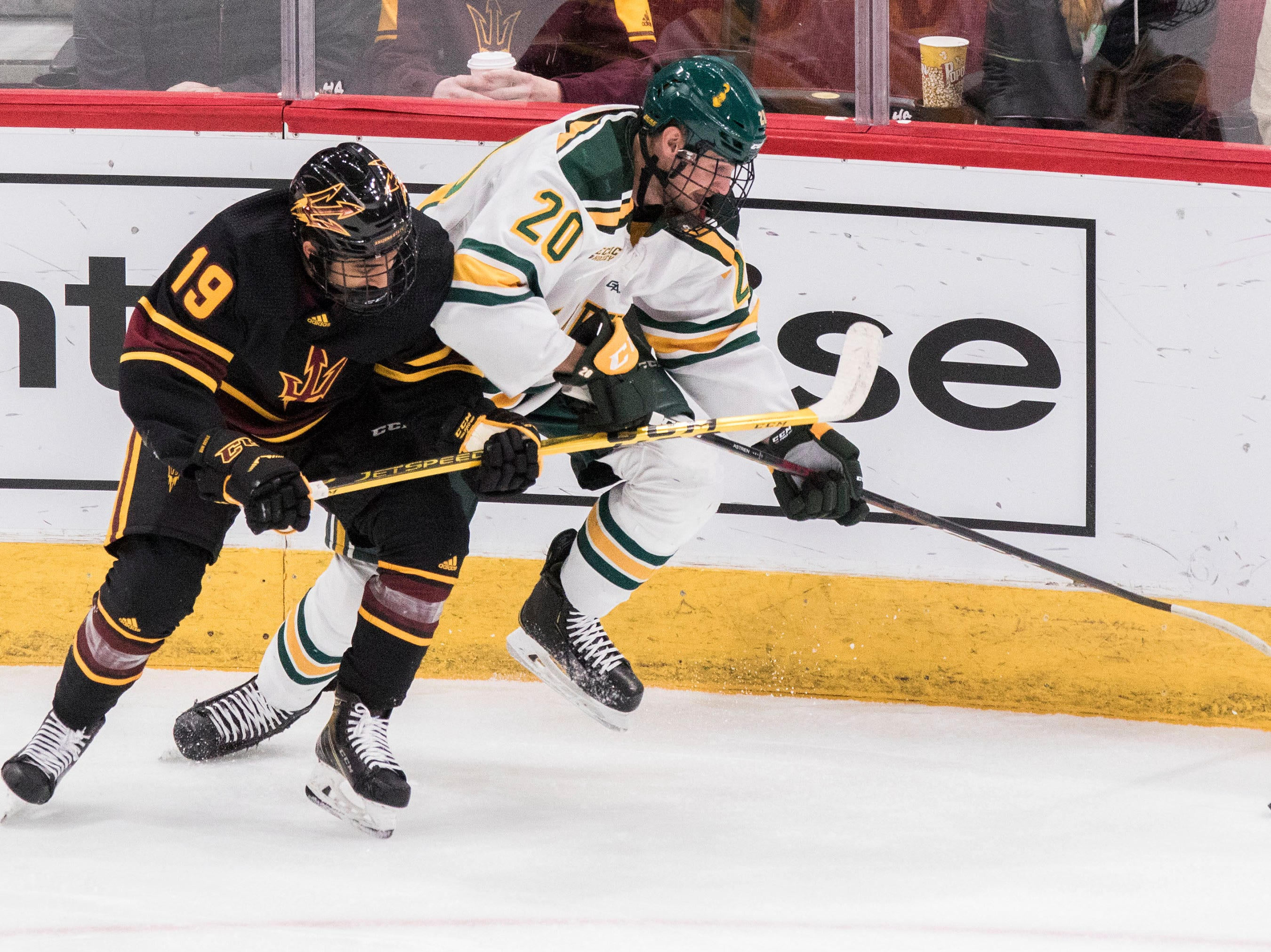 Arizona State University's Jordan Sandhu (19) fights for the puck with Clarkson's Jere Astren (20) during the first period of their game in the 2018 Desert Hockey Classic in Glendale, Friday, Dec. 28, 2018.