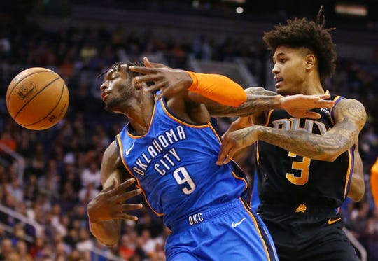 Phoenix Suns forward Kelly Oubre Jr. battles for the loose ball with Oklahoma City Thunder forward Jerami Grant on Dec. 28 at Talking Stick Resort Arena in Phoenix.