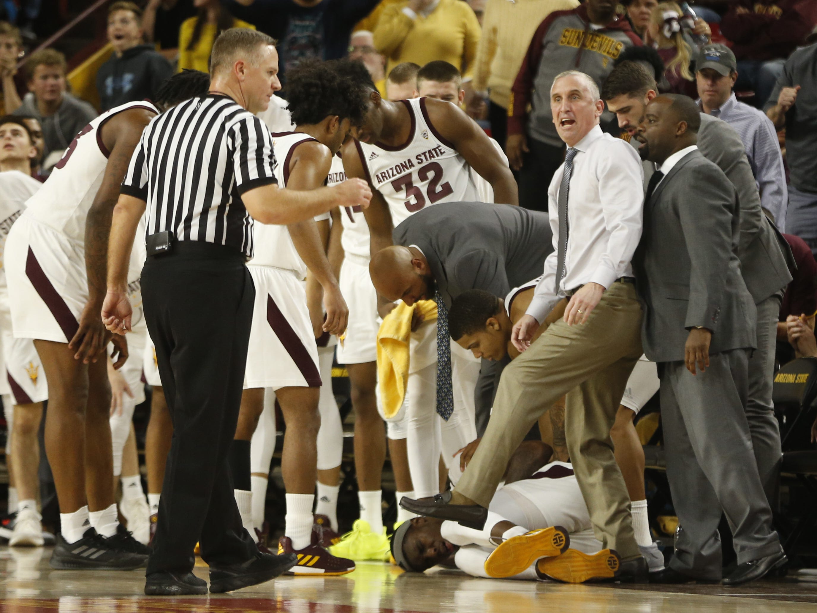 ASU's head coach Bobby Hurley argues with an official as forward Zylan Cheatham lays down after falling over a Princeton player during the first half at Wells Fargo Arena in Tempe, Ariz. on December 29, 2018.